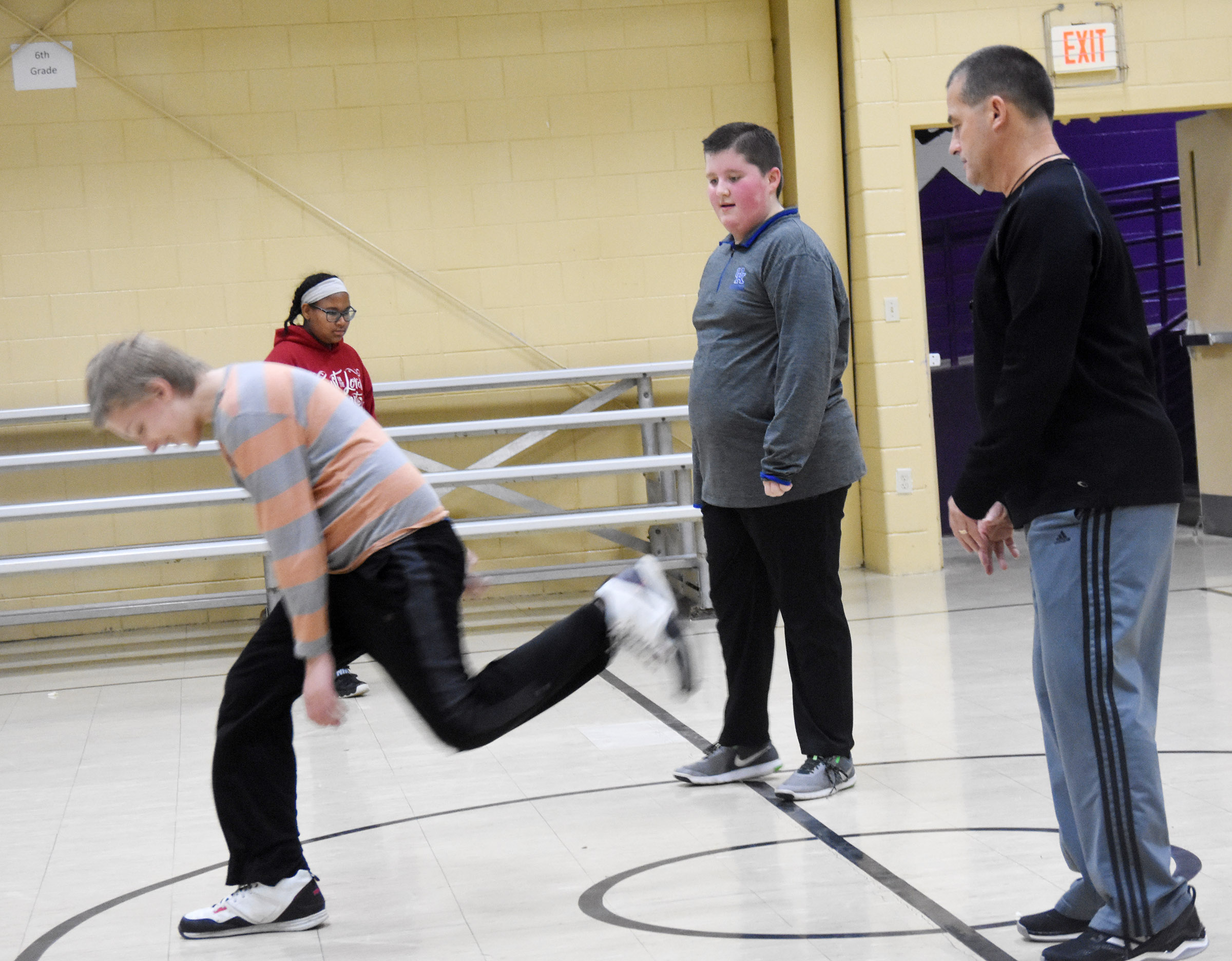 CMS substitute teacher Lynn Kearney watches as students practice their long jump. Pictured are, from left, sixth-graders Jacob Releford, KyAshia Mitchell and Luke McDonald.