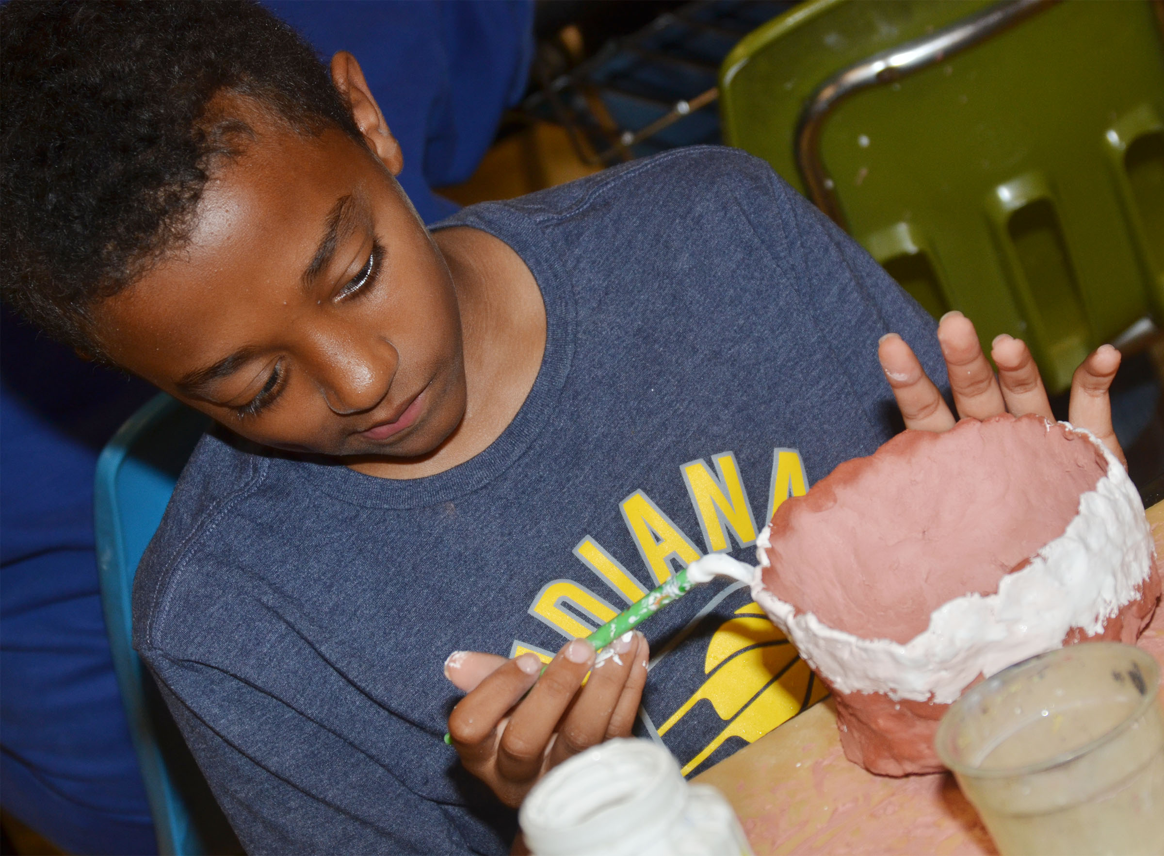 CMS sixth-grader Zamar Owens paints his pot.