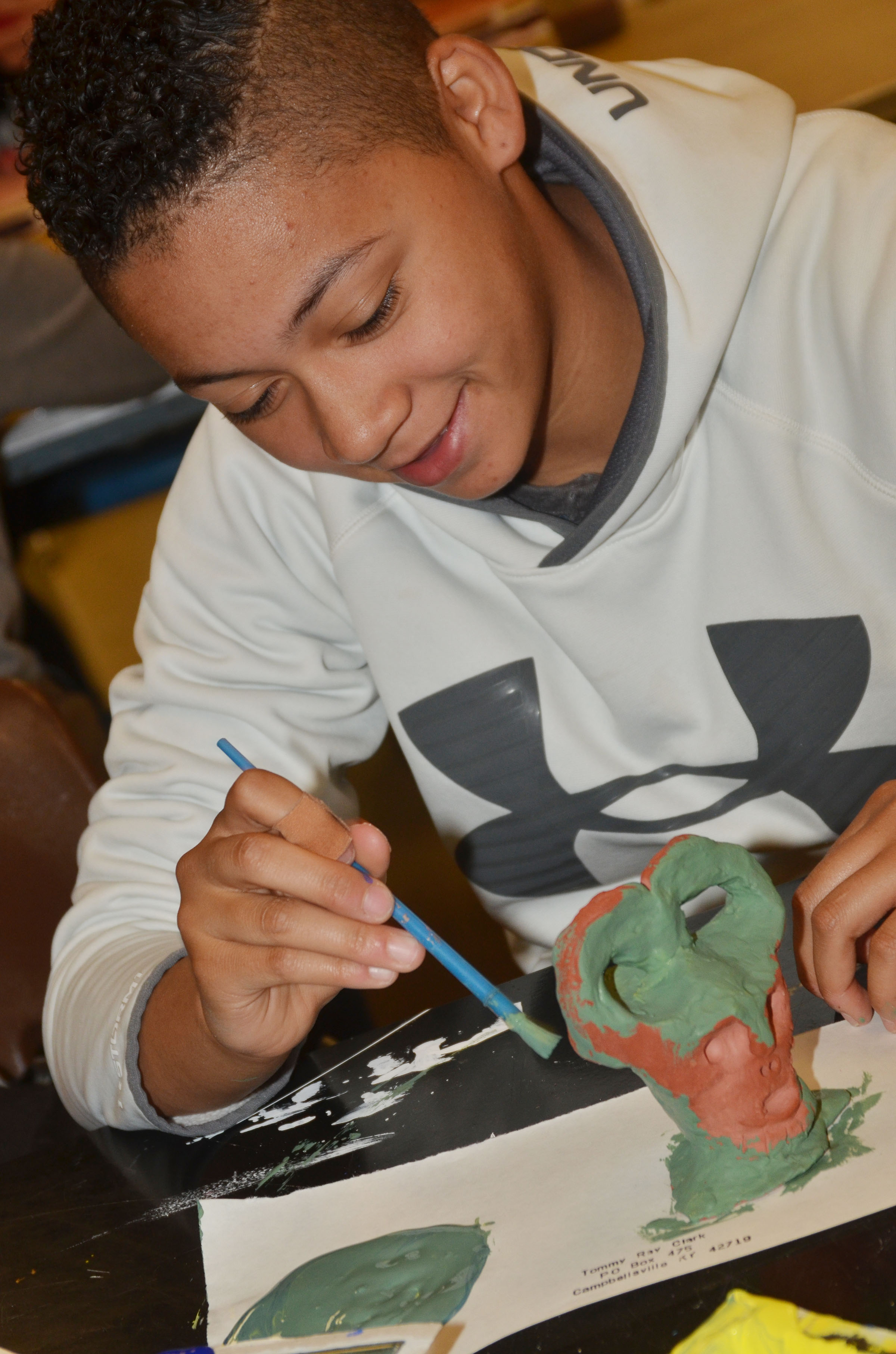 CMS eighth-grader Taylor Whaley paints her pottery.