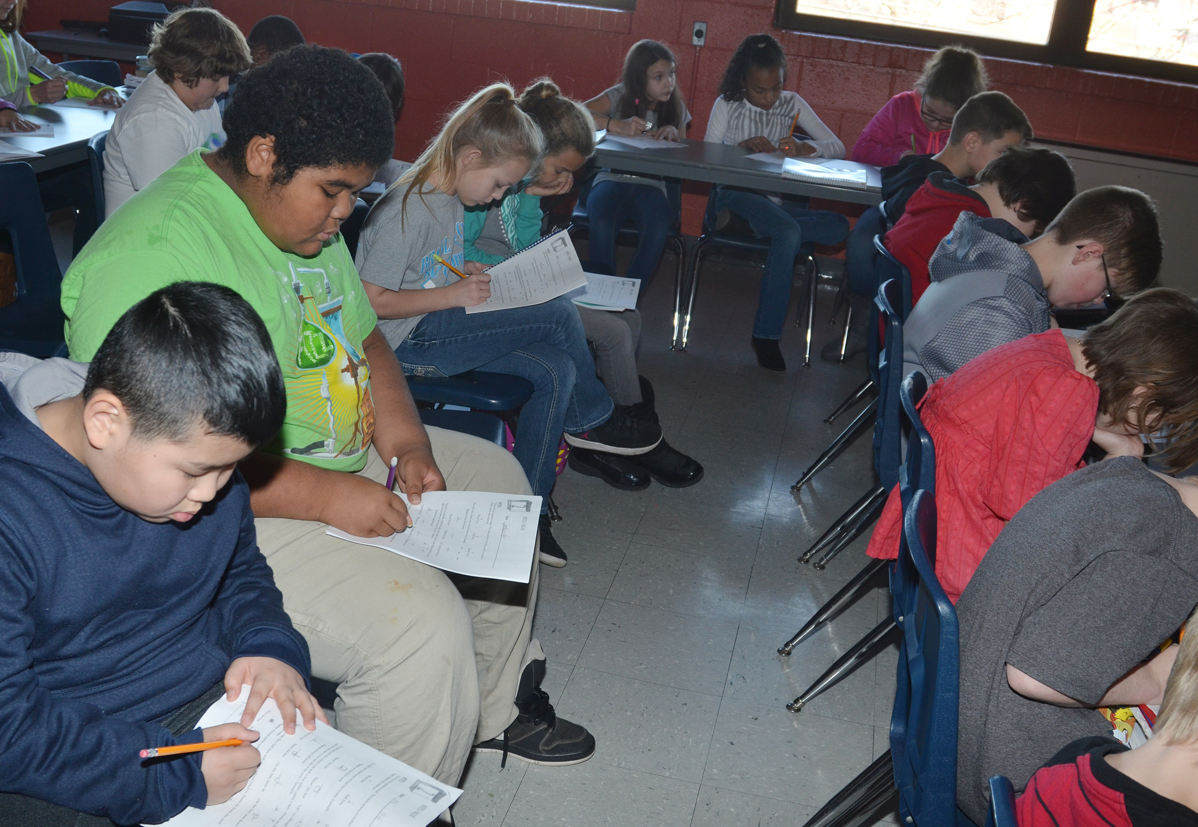 CMS fourth-graders Zhi Chen, at left, Zaedyn Branch and their classmates practice writing musical notes.