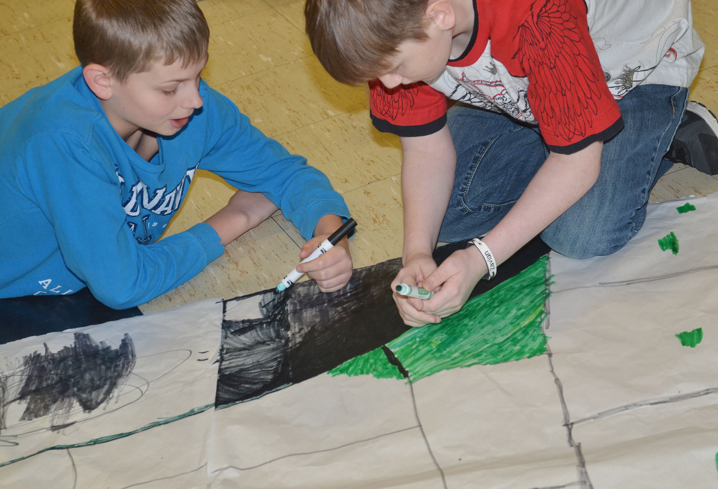 CMS sixth-graders Ethan Bright, at left, and Zavian McColley color a scene from their book.