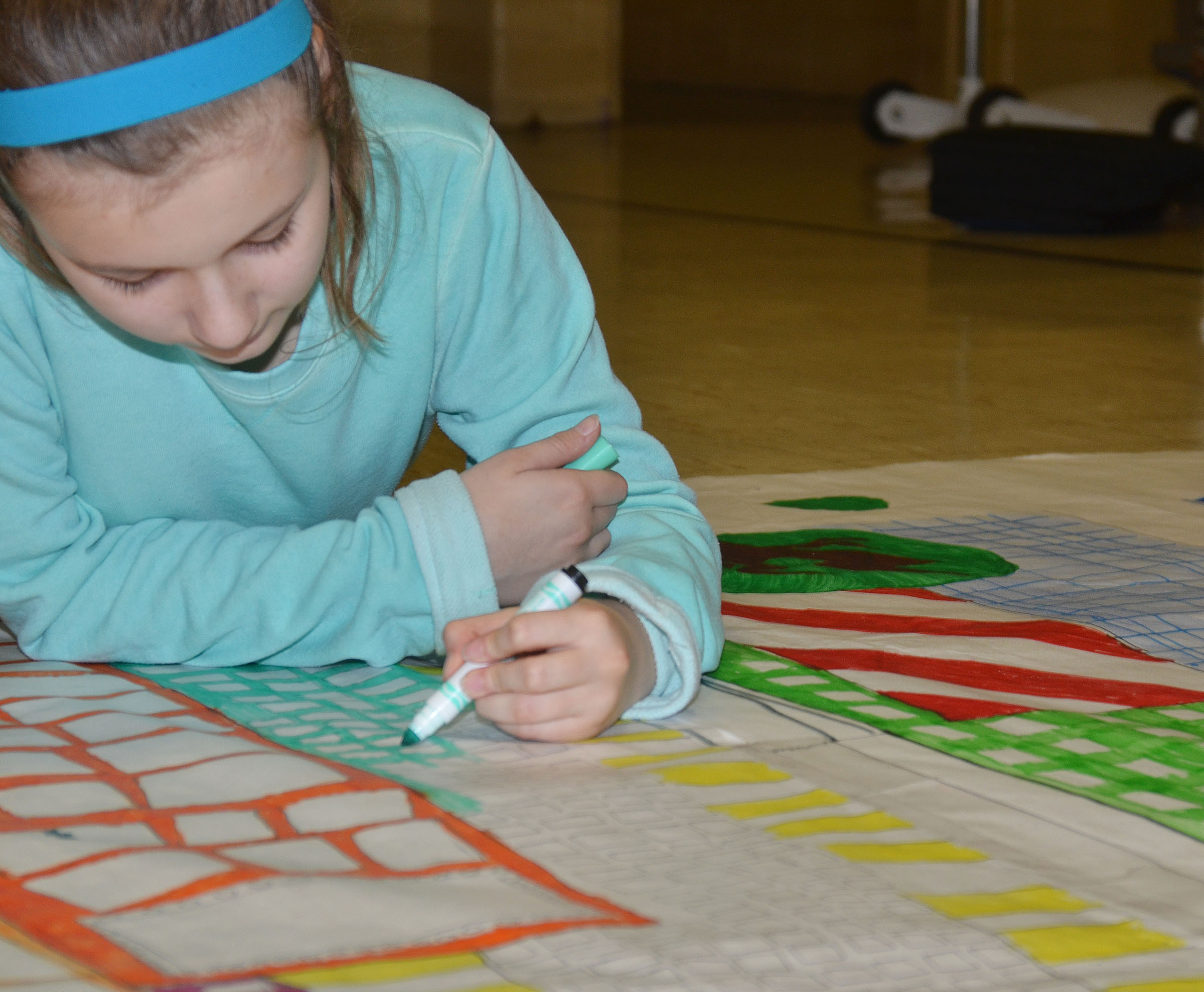 CMS seventh-grader Serenity Ford colors a scene from her book.