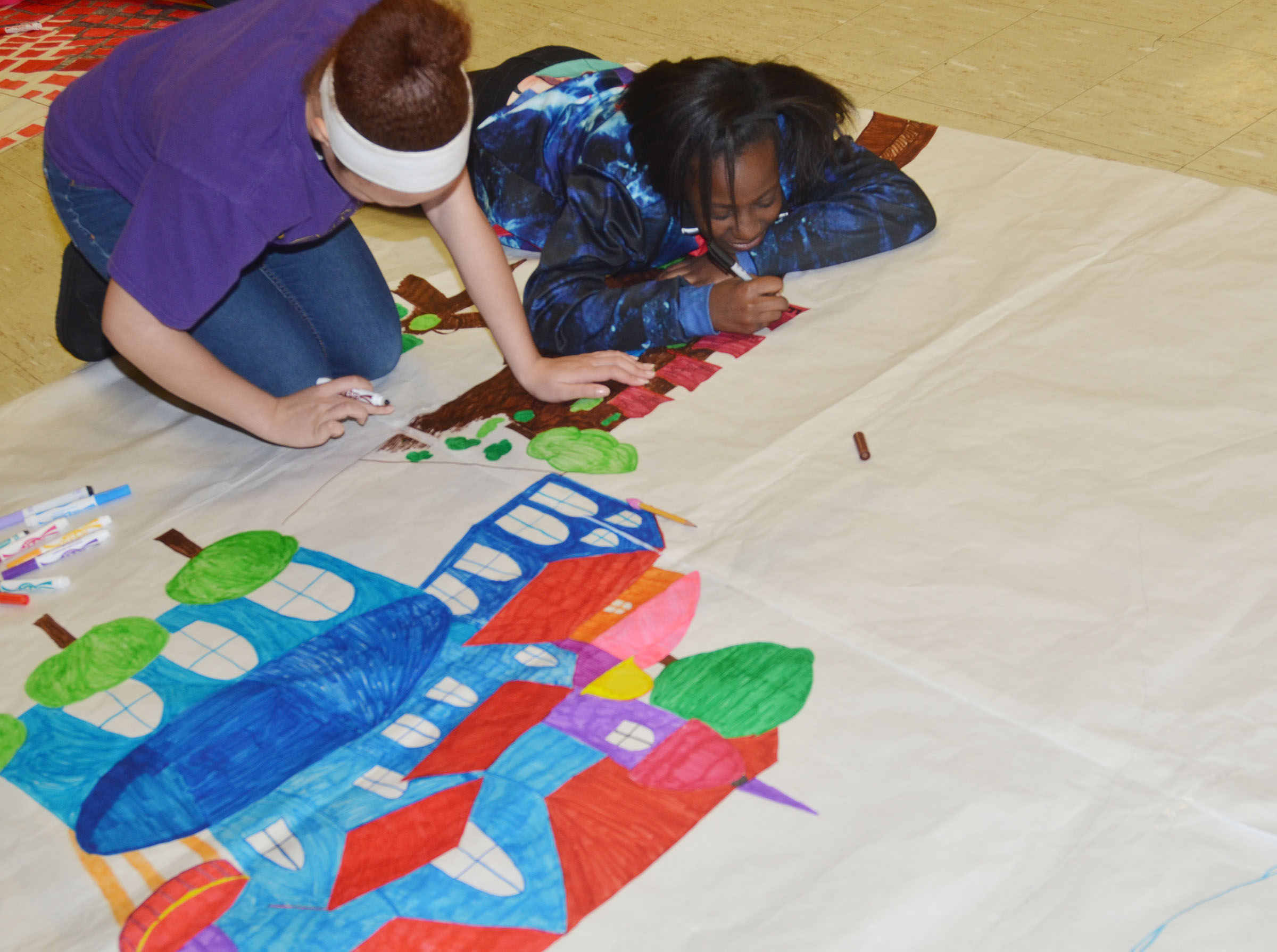 CMS seventh-graders Kitana Taylor, at left, and Myricle Gholston color a scene from their book.