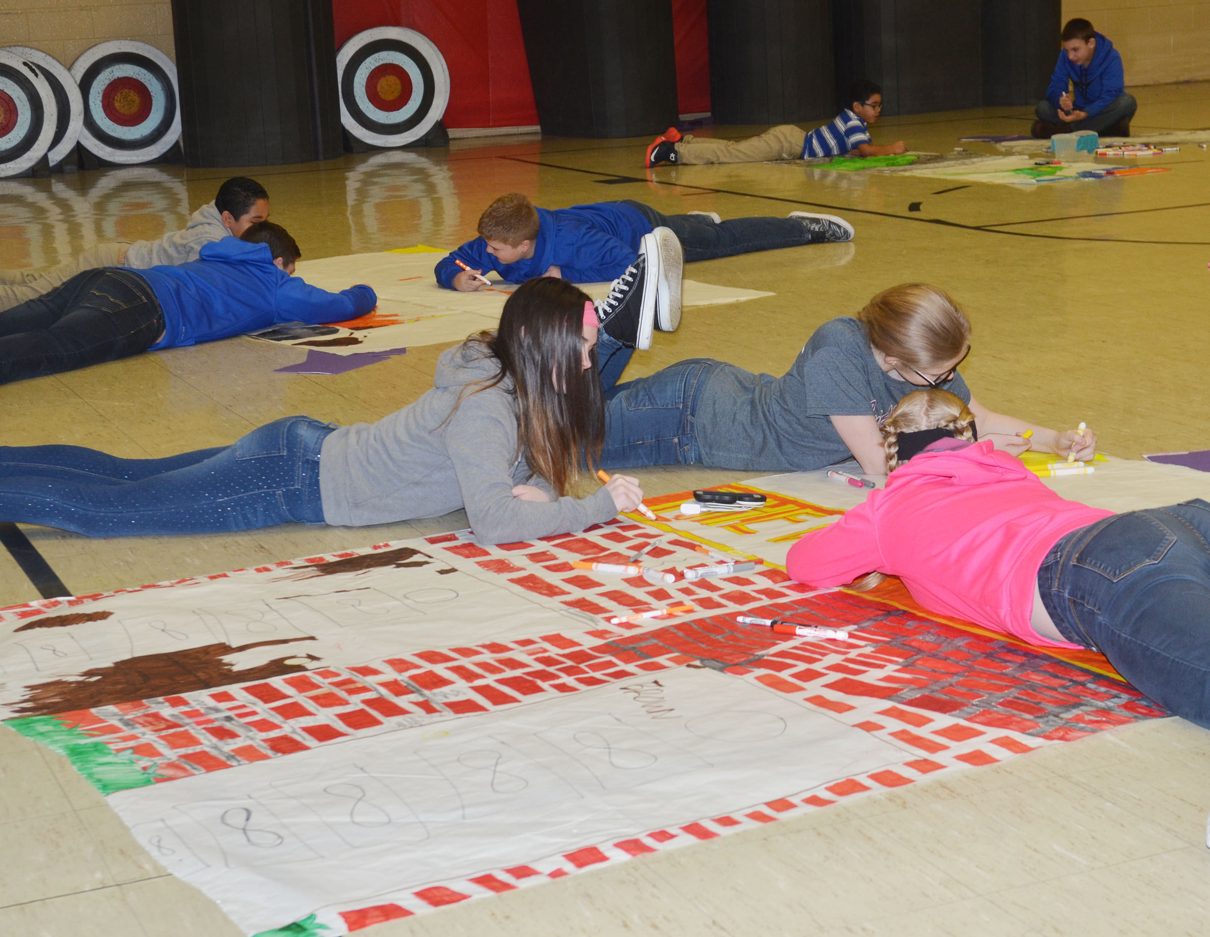 CMS students work in groups to draw and color scenes from their books.