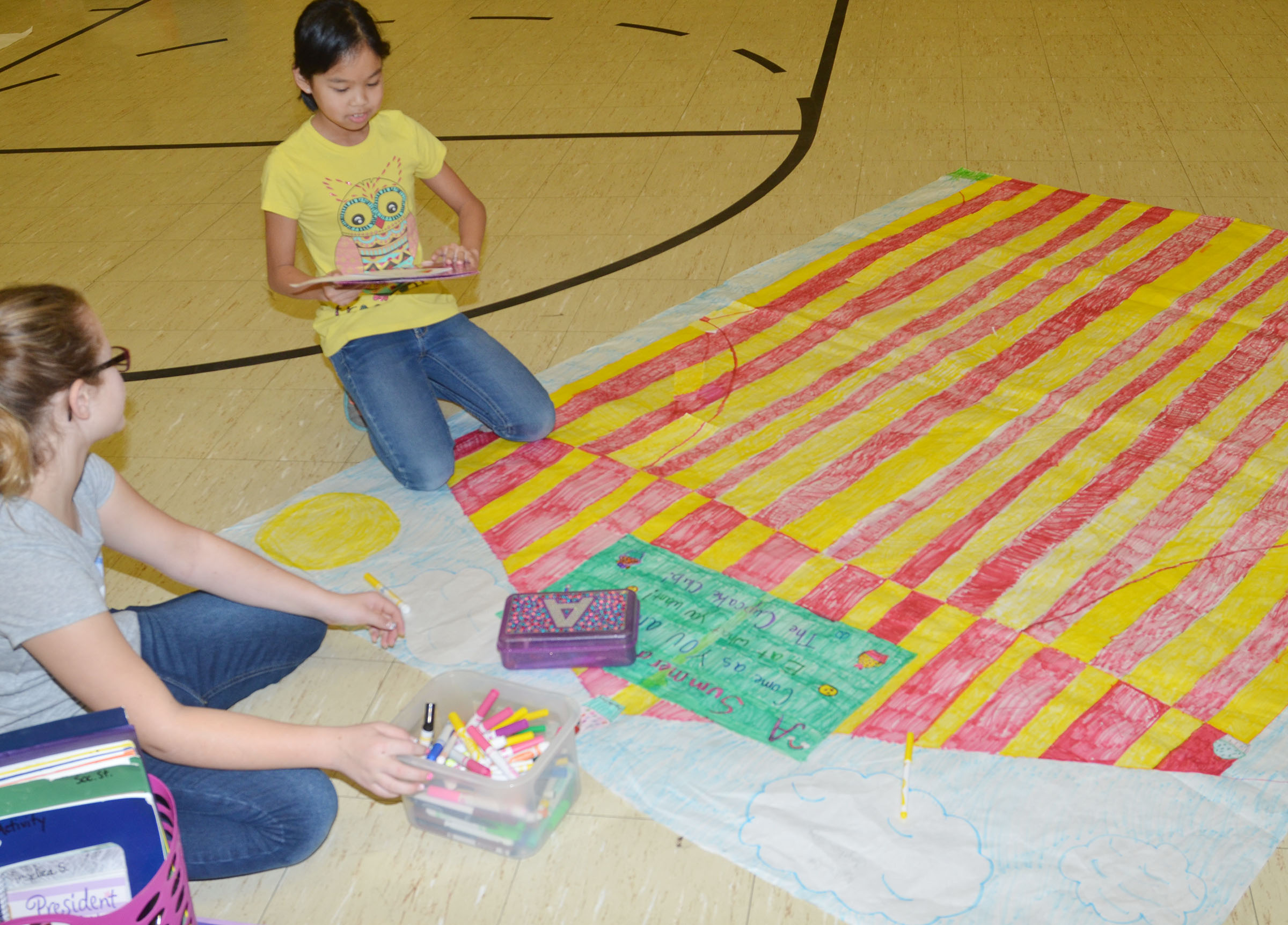 CMS fifth-graders Karlie Cox, at left, and Angelica Seng talk about their drawing.