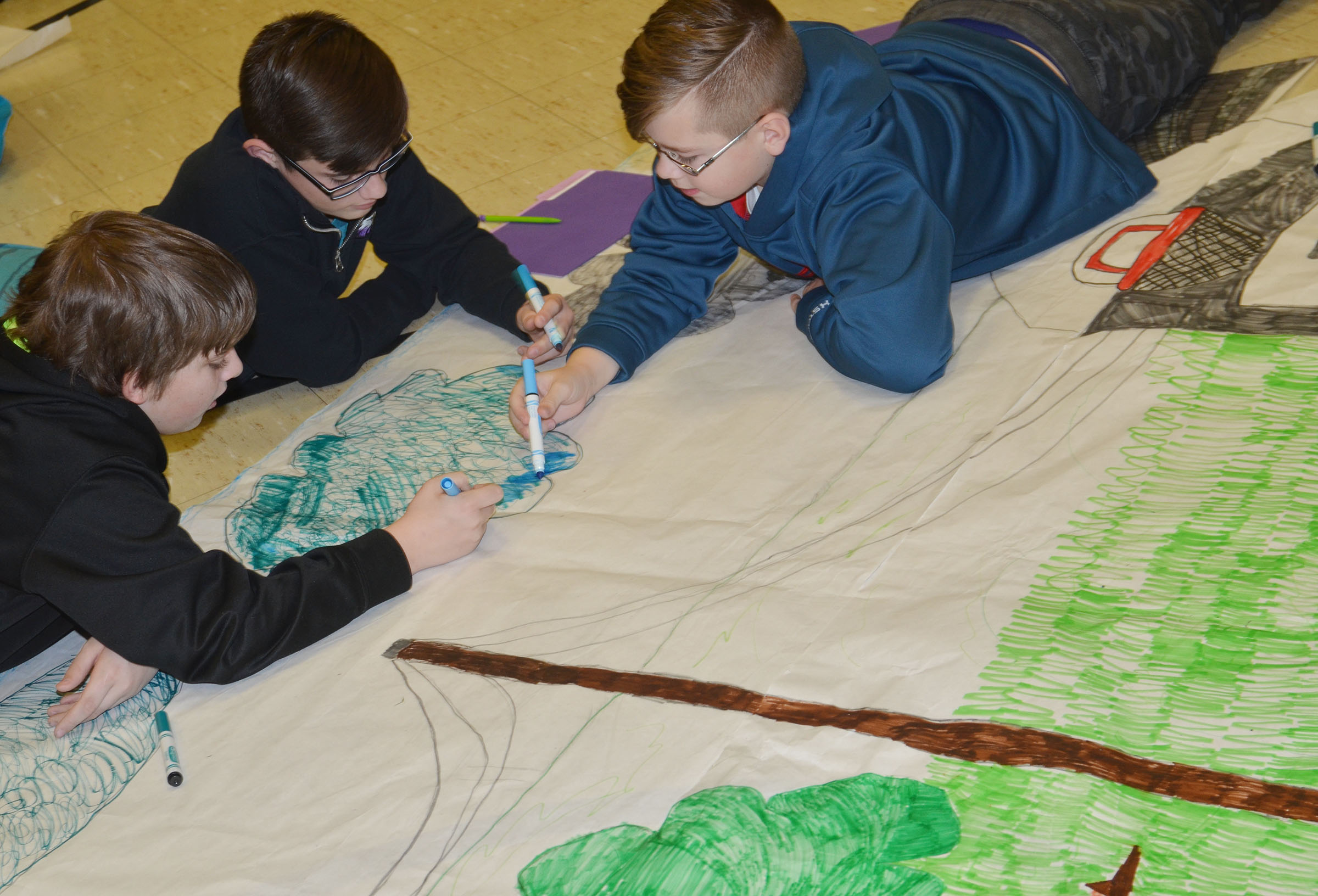 From left, CMS fifth-graders Ashton Davis, Isaac Garrison and Jovi Bowen color a scene from their book.