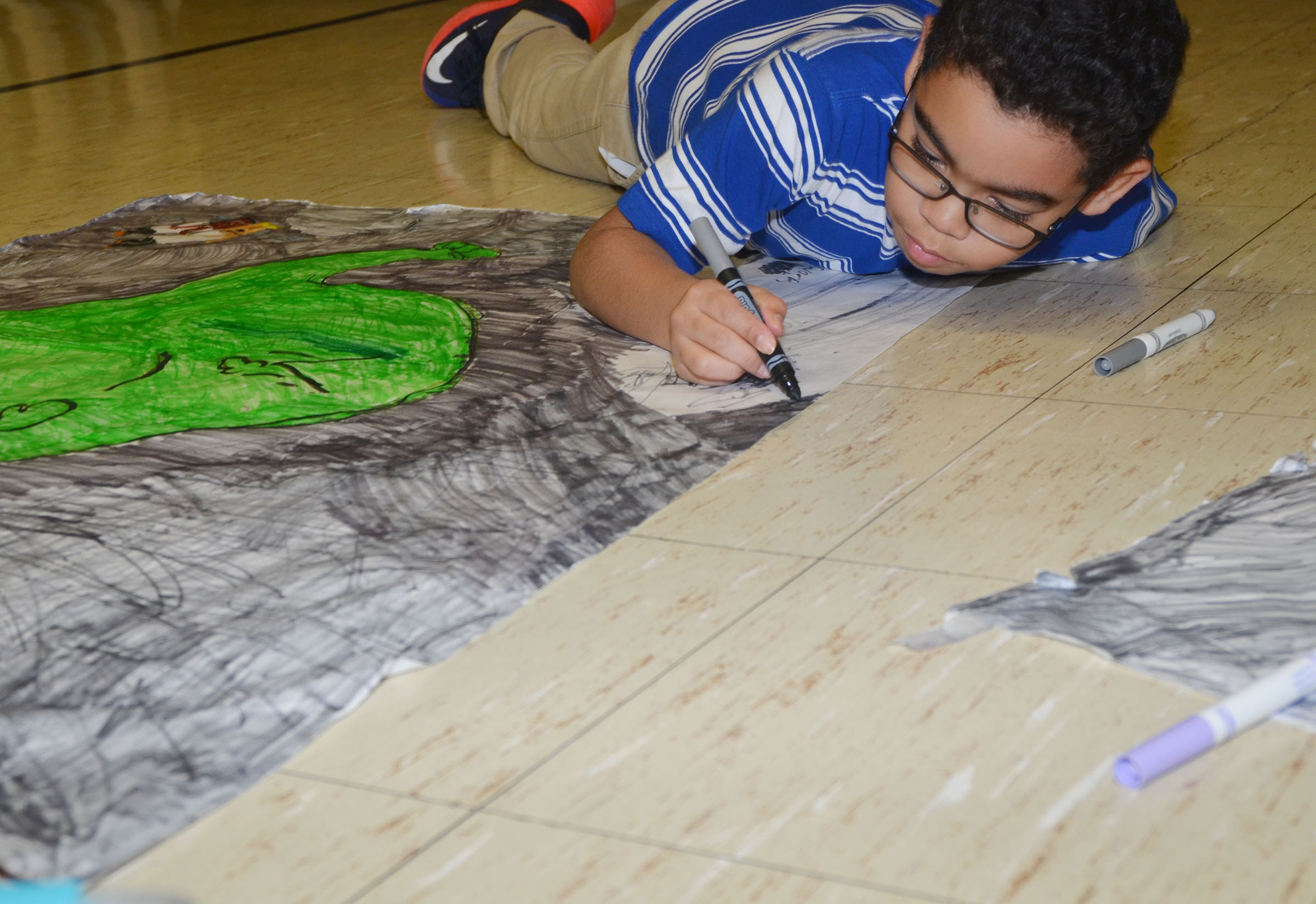 CMS fifth-grader Diego Noyola colors a scene from his book.