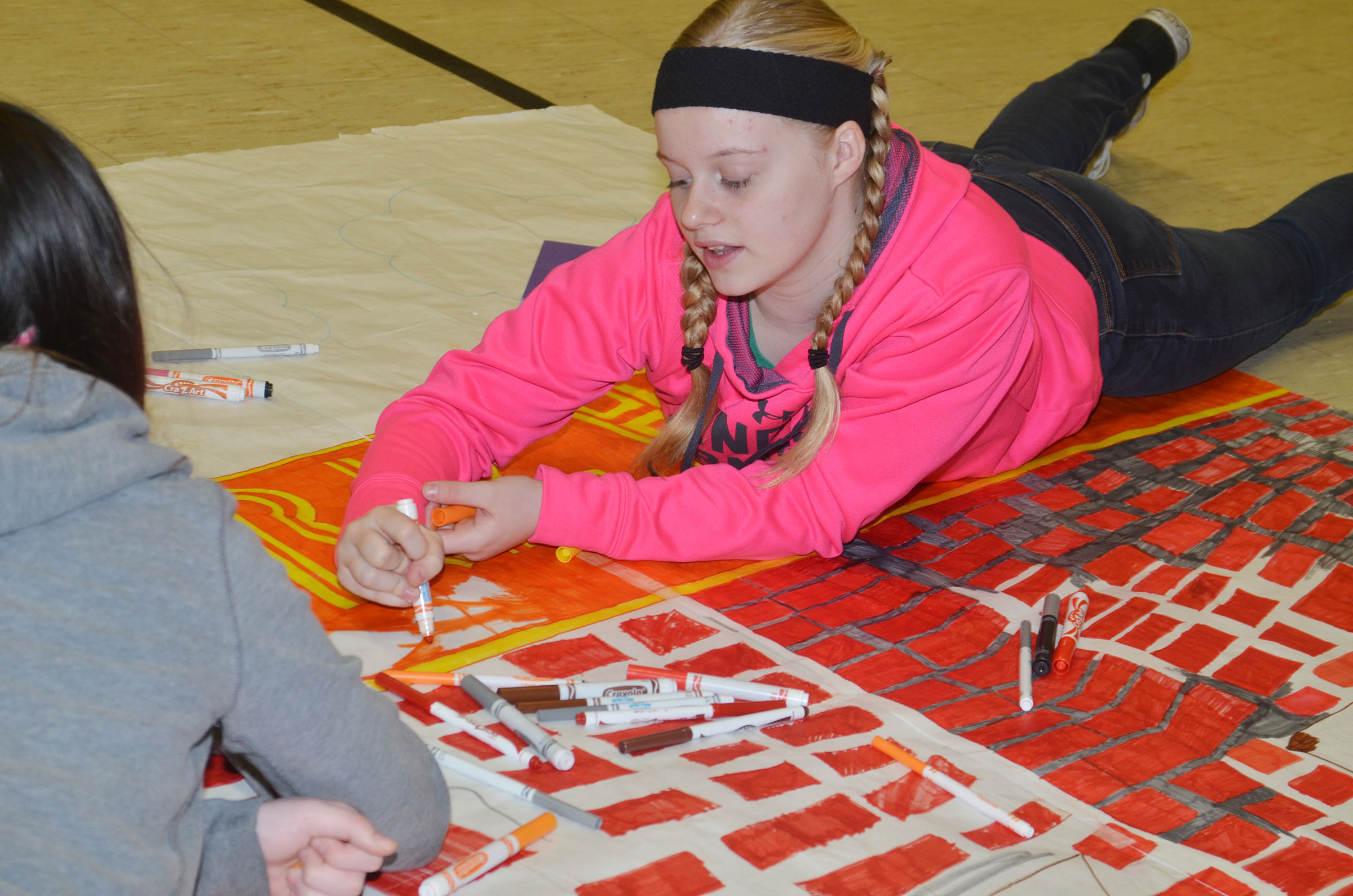 CMS seventh-grader Gabby Skaggs colors a scene from her group's book.