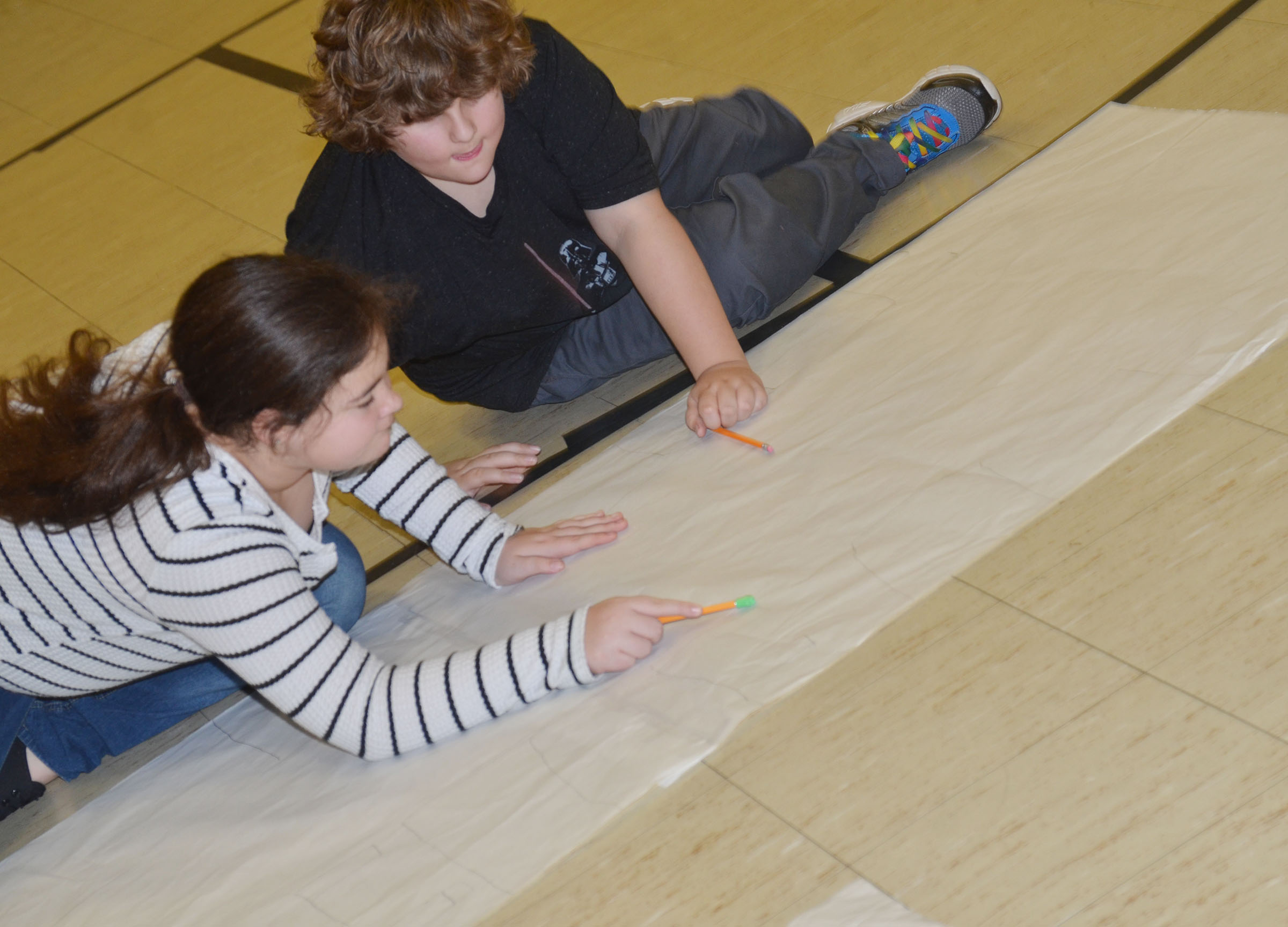 CMS fifth-grader Brianna Dobson, at left, and fourth-grader Zeke Harris sketch a scene from their book.