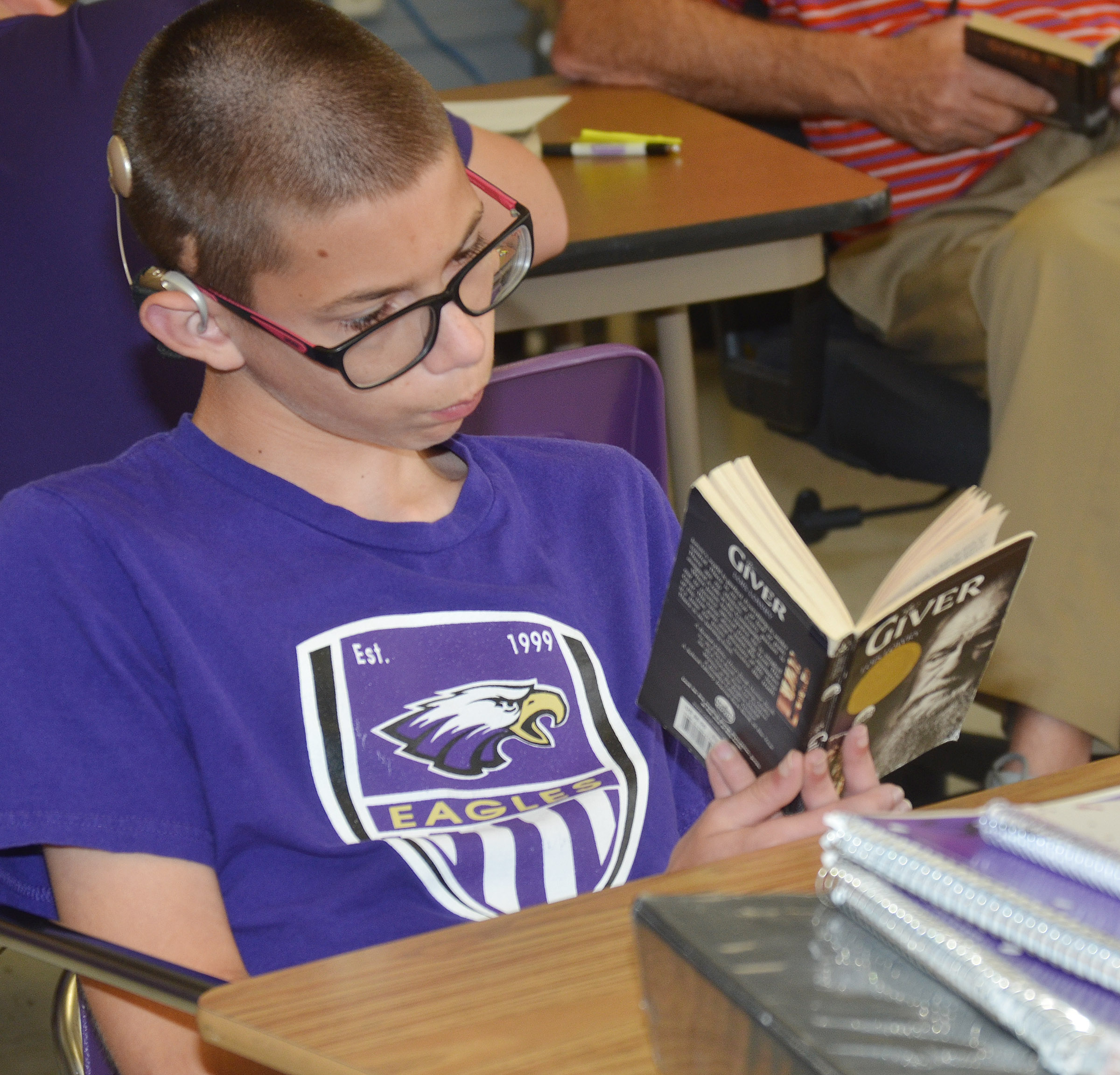 "CMS eighth-grader Grant Lawson reads ""The Giver."""