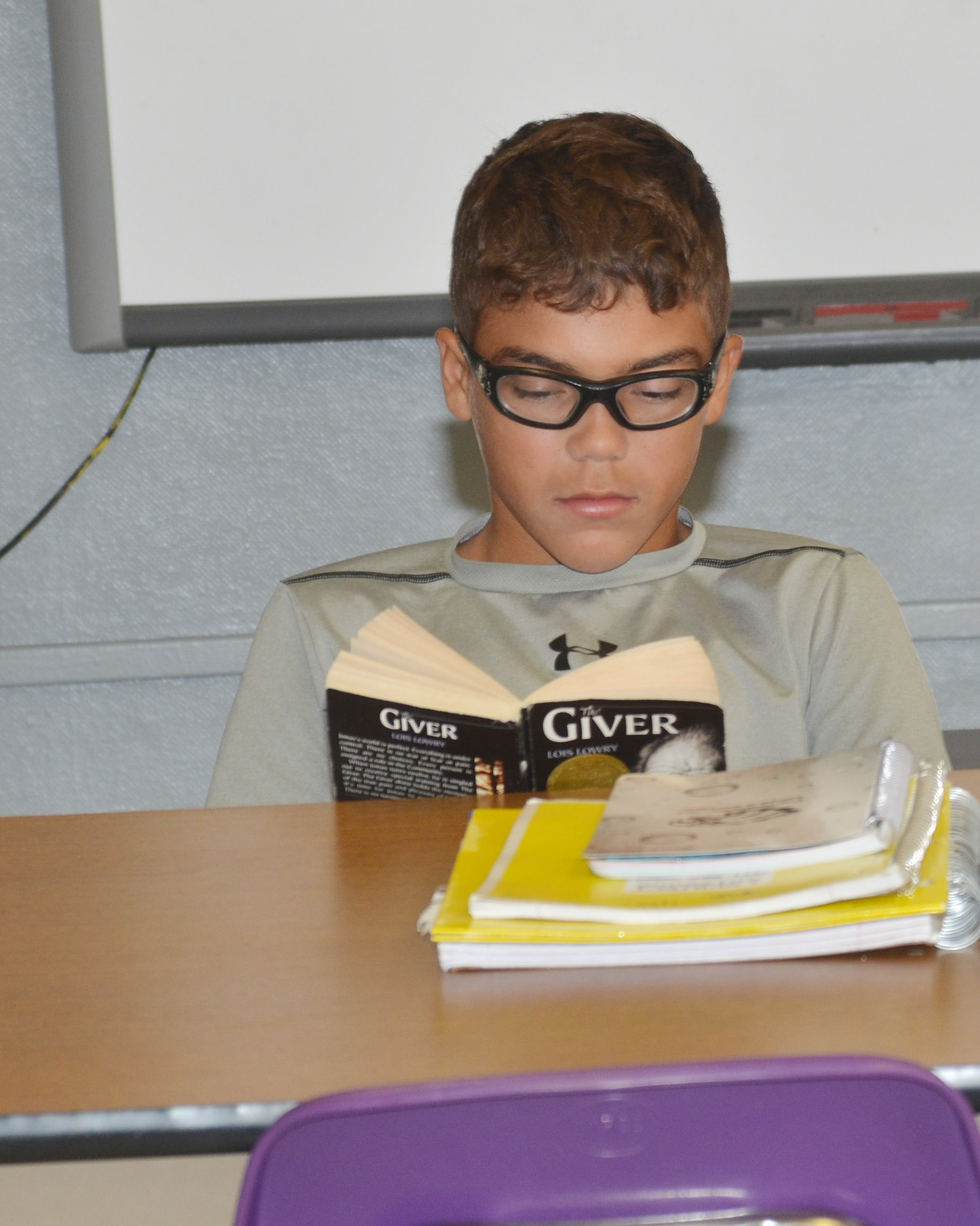 "CMS eighth-grader Logan Phillips reads ""The Giver."""