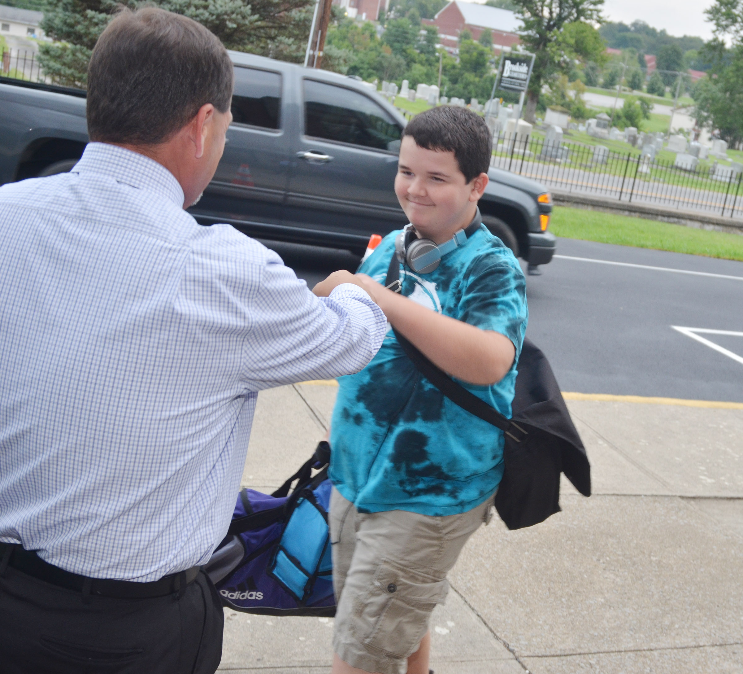 Campbellsville Independent Schools Director of Federal Programs Ricky Hunt greets his son, Adin, on his second day of eighth grade.