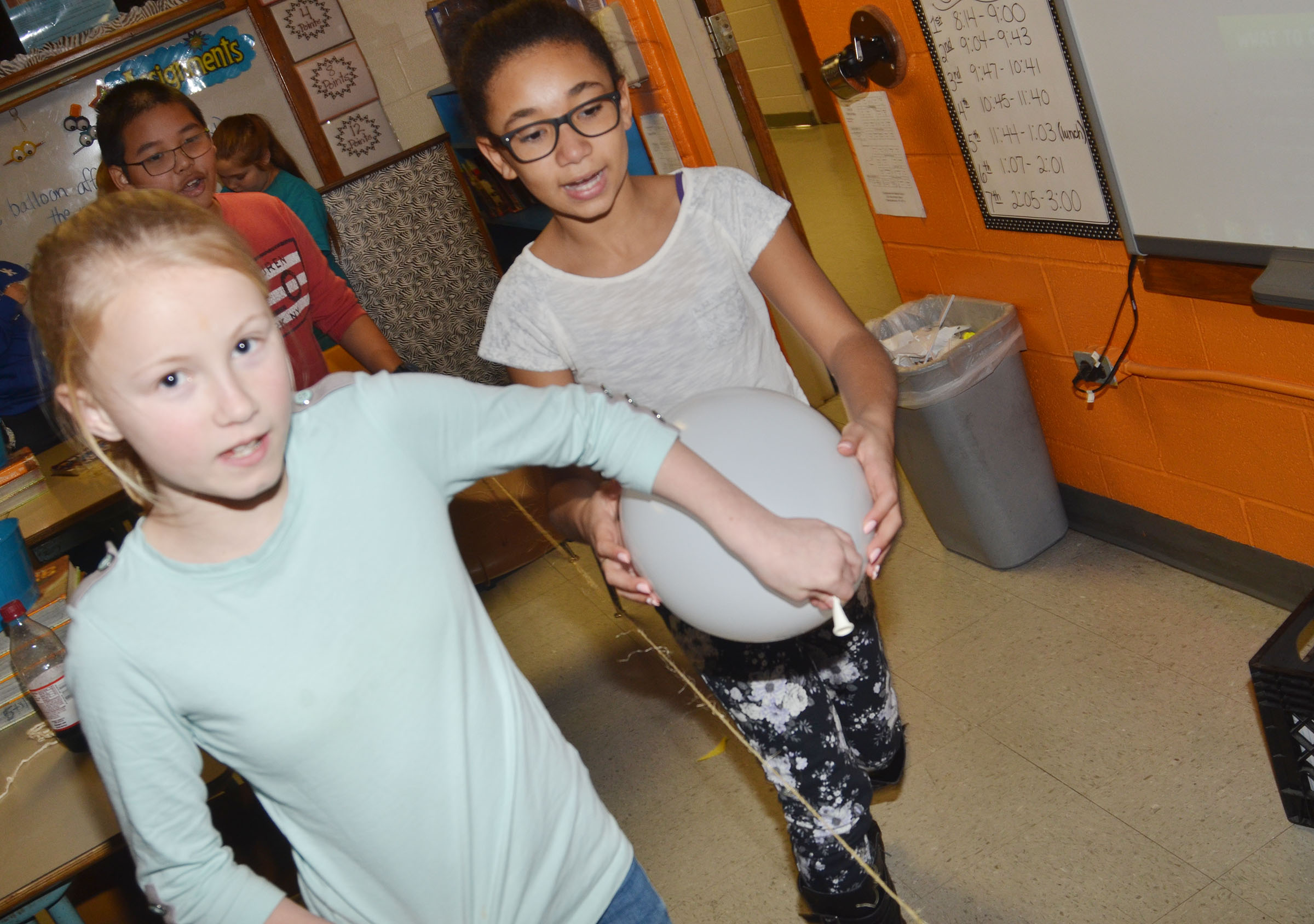 CMS fifth-graders, from left, Brianna Atwood, Kewin Dong and Keely Thompson see how far their balloon rocket will travel.