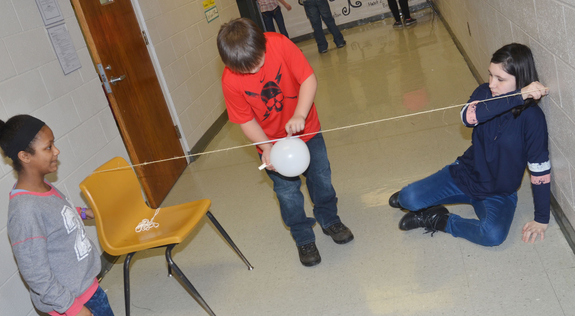 CMS fifth-graders, from left, Camilla Taylor, Leo Lamer and Kaylin Forbis launch their balloon rocket.