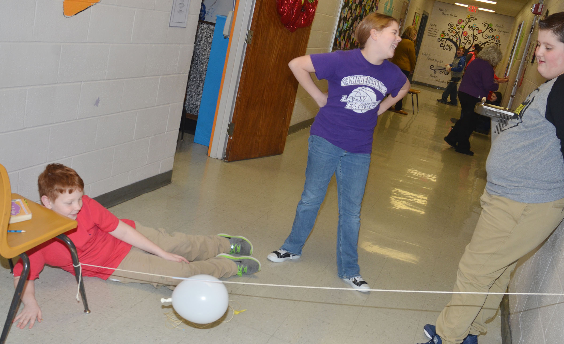 CMS fifth-graders, from left, Conner Rinehart, Layla Steen and Luke McDonald launch their balloon rocket.