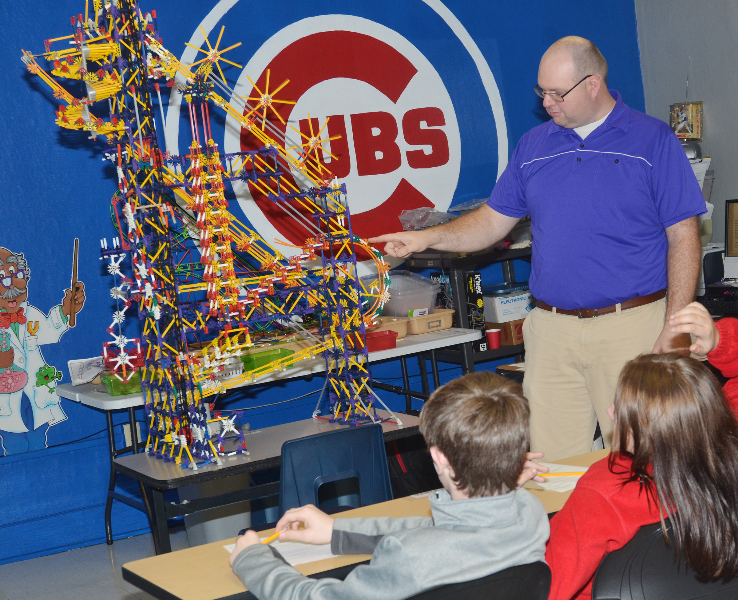 CMS seventh-grade science teacher Steven Gumm illustrates how gravity makes a ball travel through this ball dropper machine, which he built.