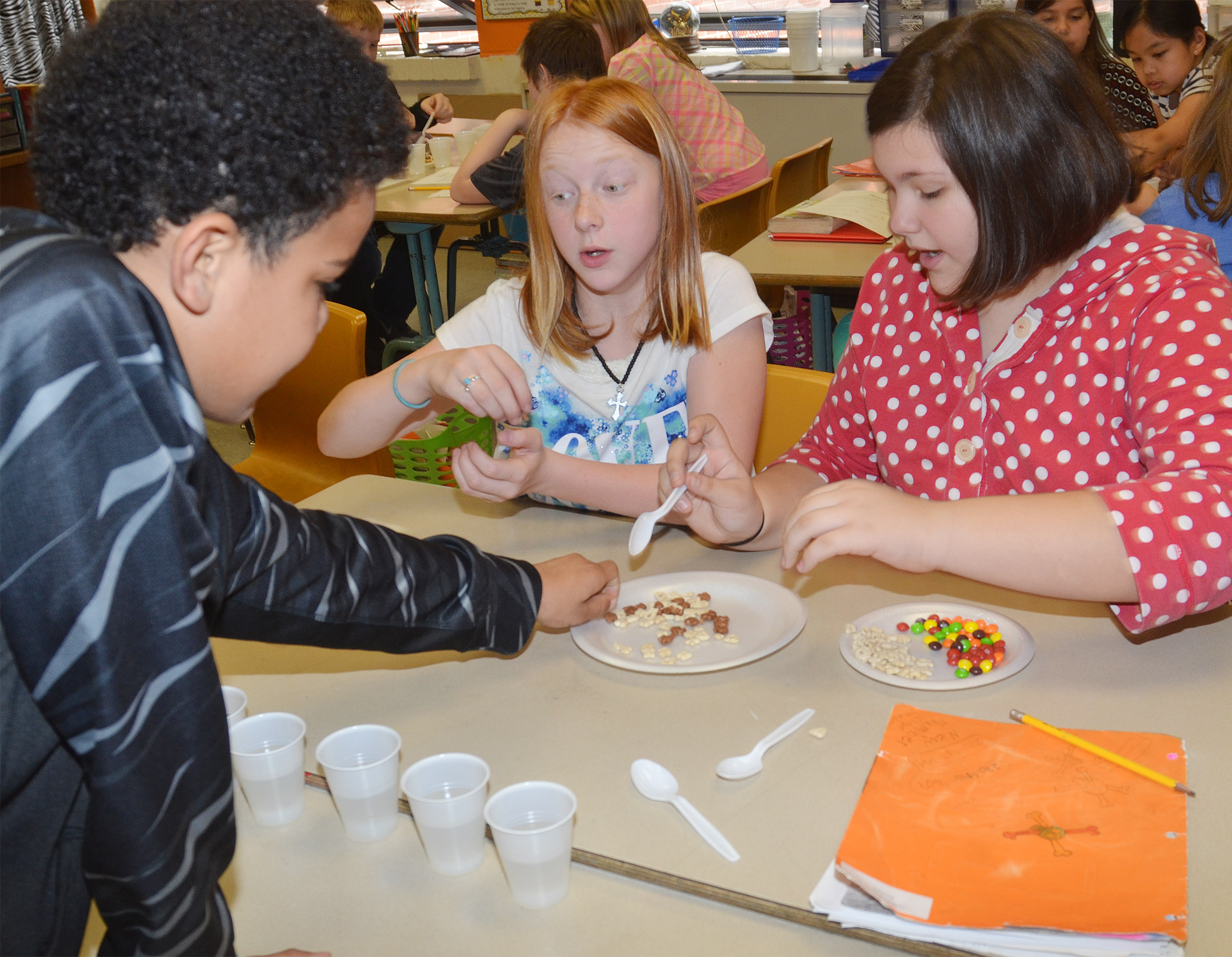 From left, CMS fifth-graders Tashaun Hart, Kaydence Wethington and Allison Sumners separate their mixture of snack foods.