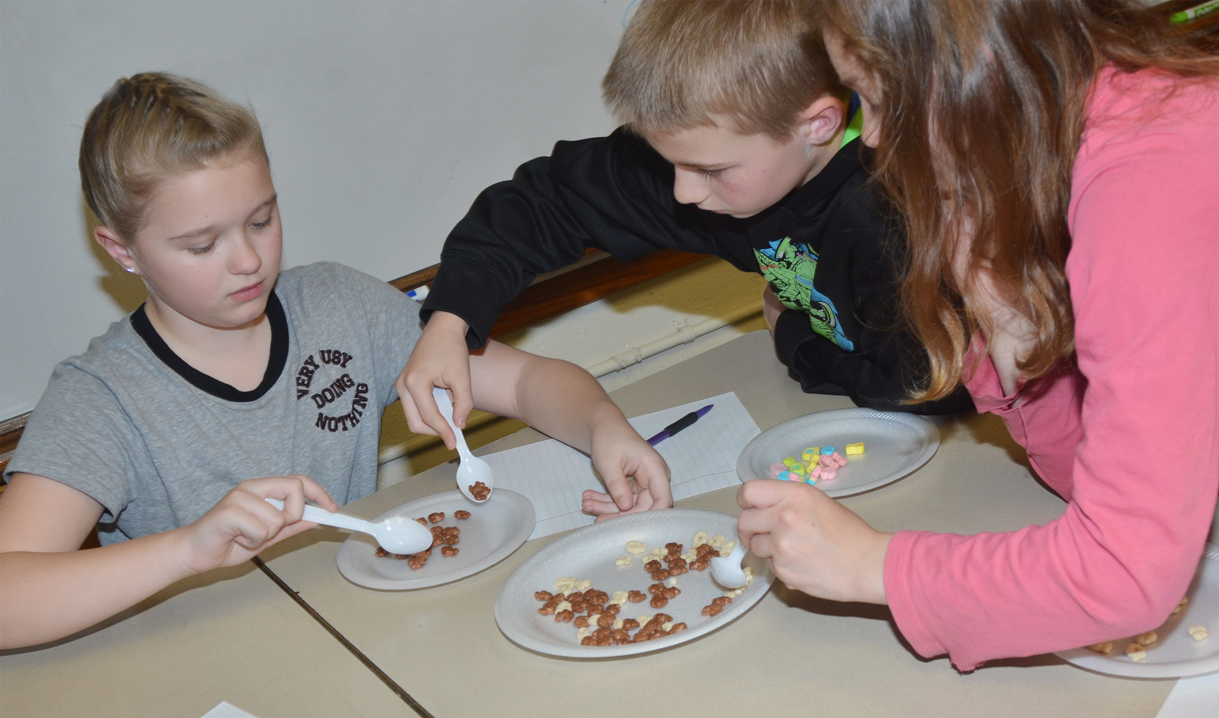 From left, CMS fifth-graders Lillee Byrne, Ethan Cox and Shaylee Cox separate their mixture of snack foods.