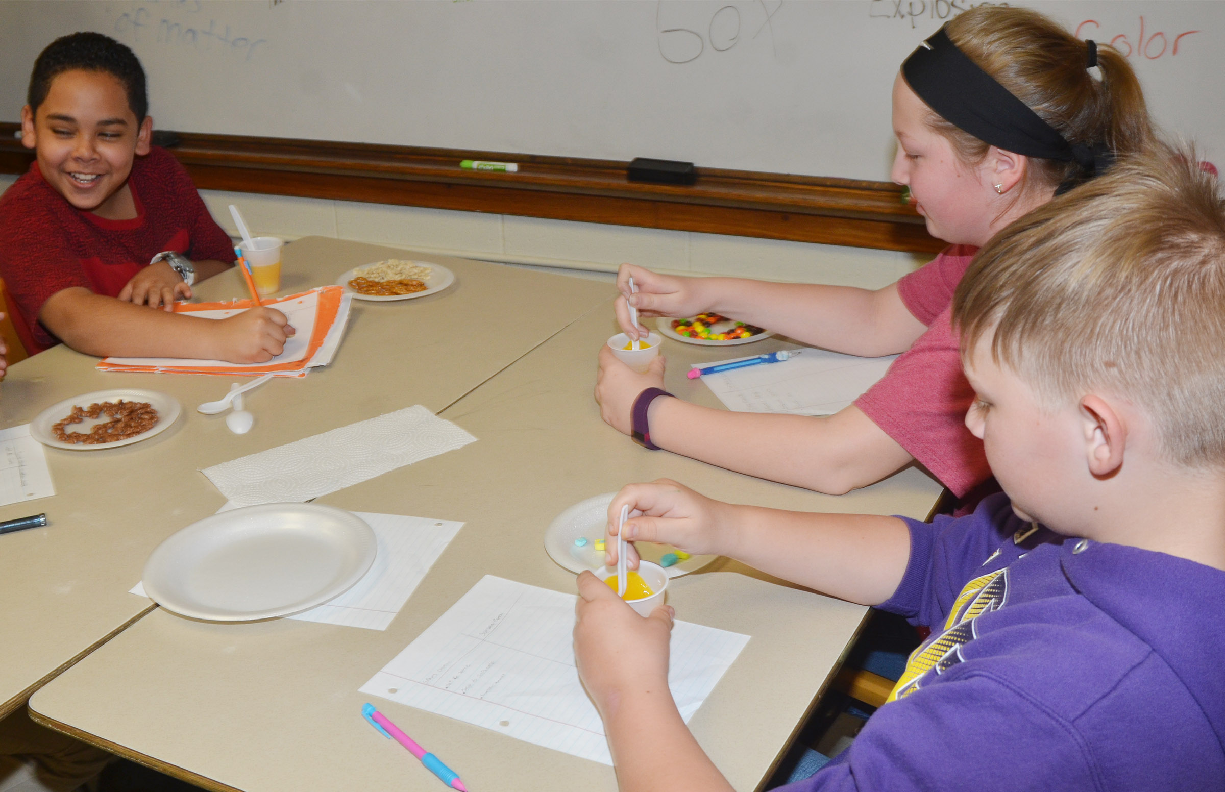 CMS fifth-graders, from left, Diego Noyola, Ava Hughes and Jesse King stir their orange drink solution.