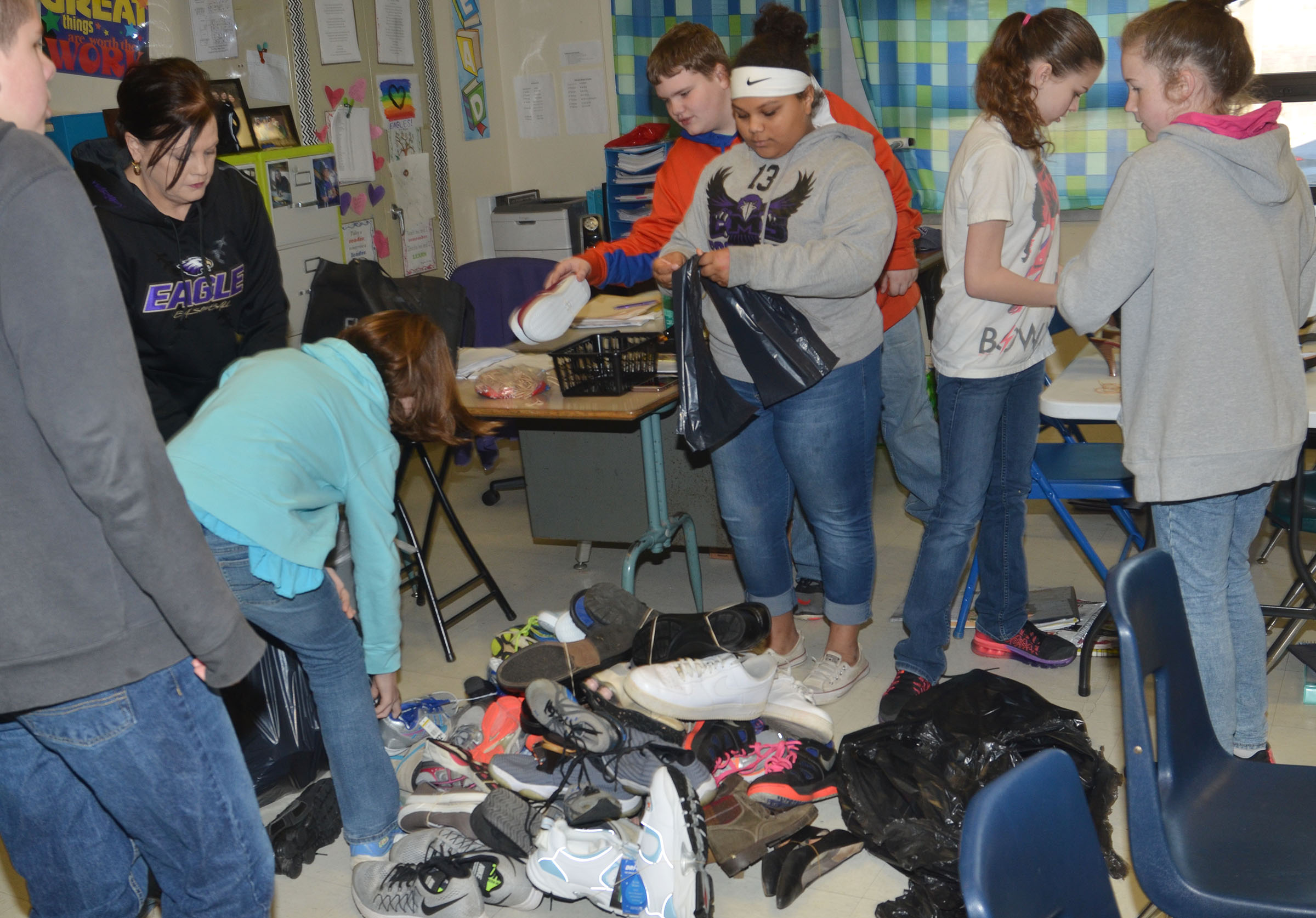 CMS sixth-grader teacher Lisa Kearney, at left, helps students sort through shoes.