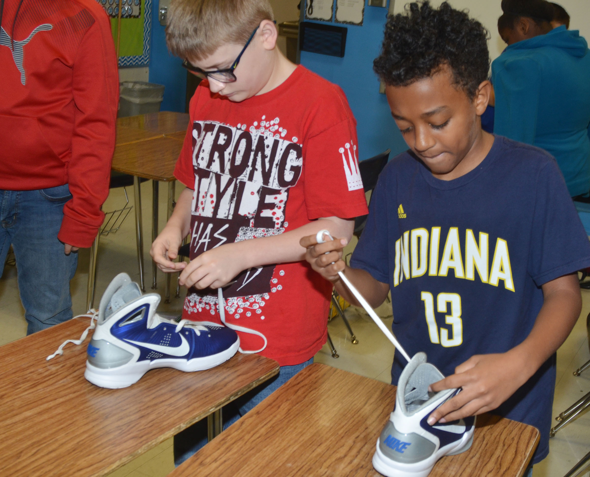 CMS sixth-graders Brady Hoosier, at left, and Zamar Owens lace a pair of shoes.