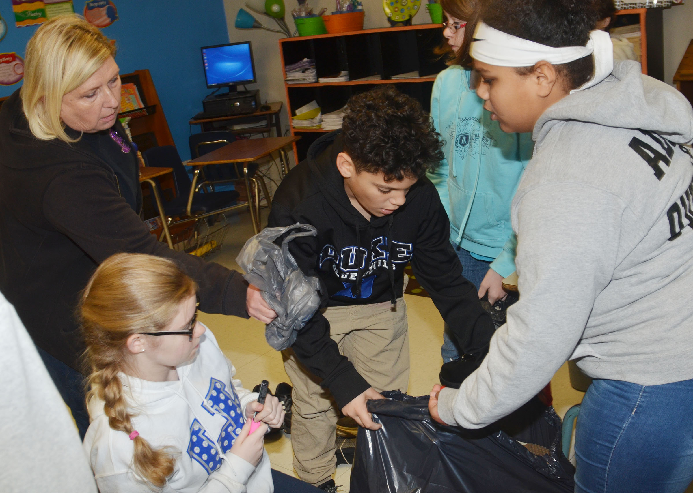 CMS sixth-grade teacher Jan Speer, at left, helps students sort through shoes.
