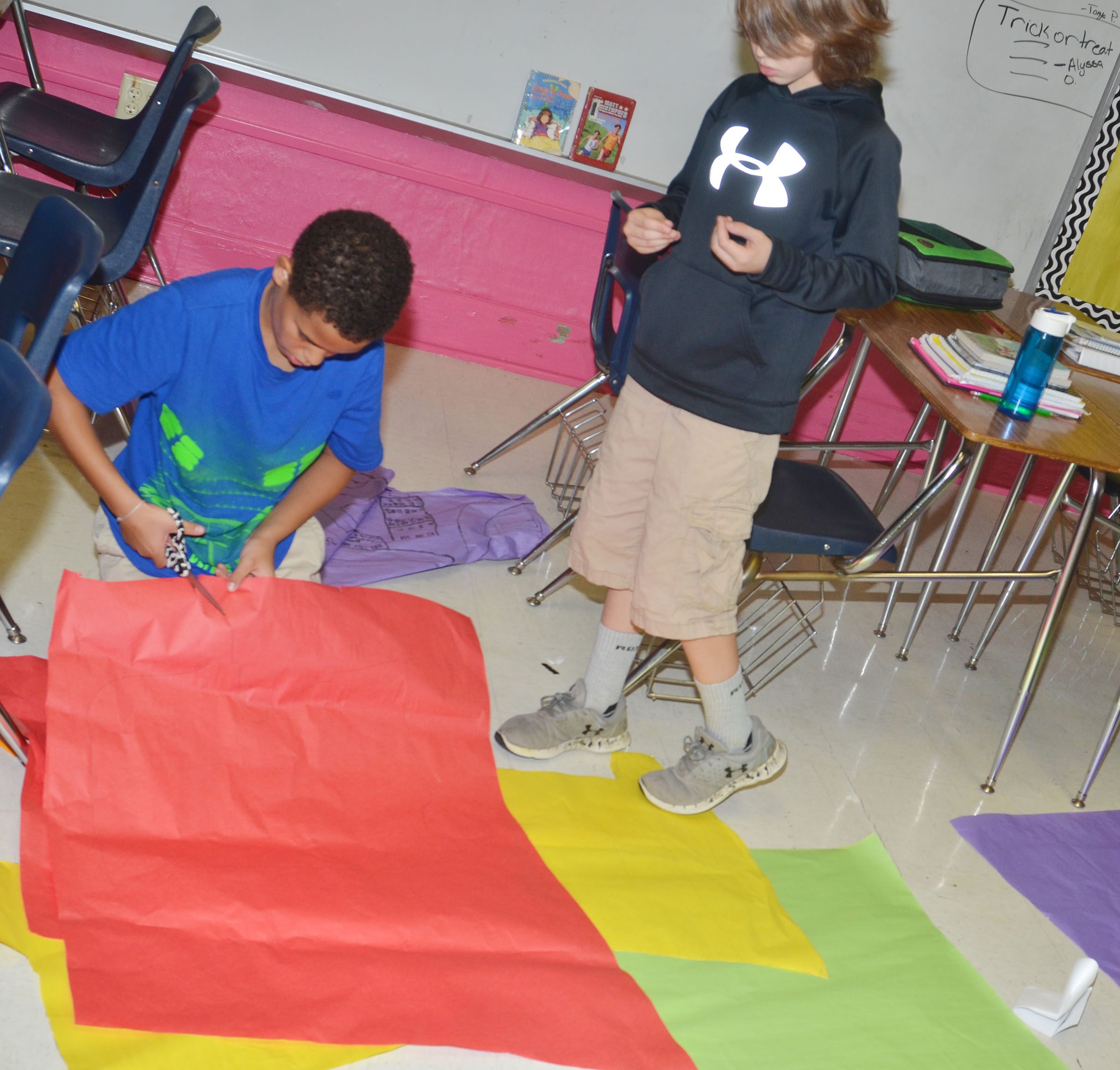 CMS sixth-graders Nasir Johnson, at left, and Logan Wilson cut out their map of the United States.