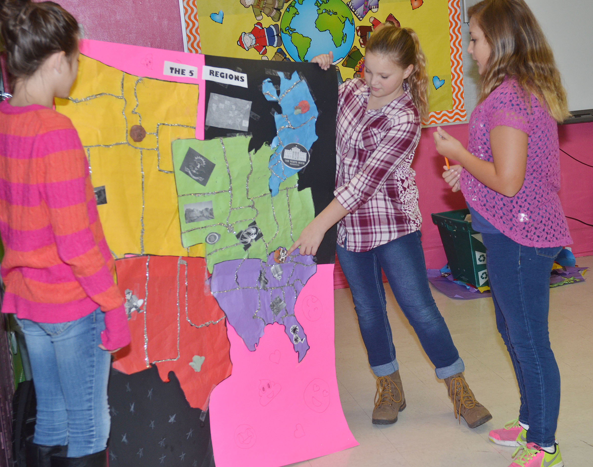 From left, CMS sixth-graders Emily Shuck, Graci Crews and Briana Davis tell their classmates about the map they made of the United States regions.