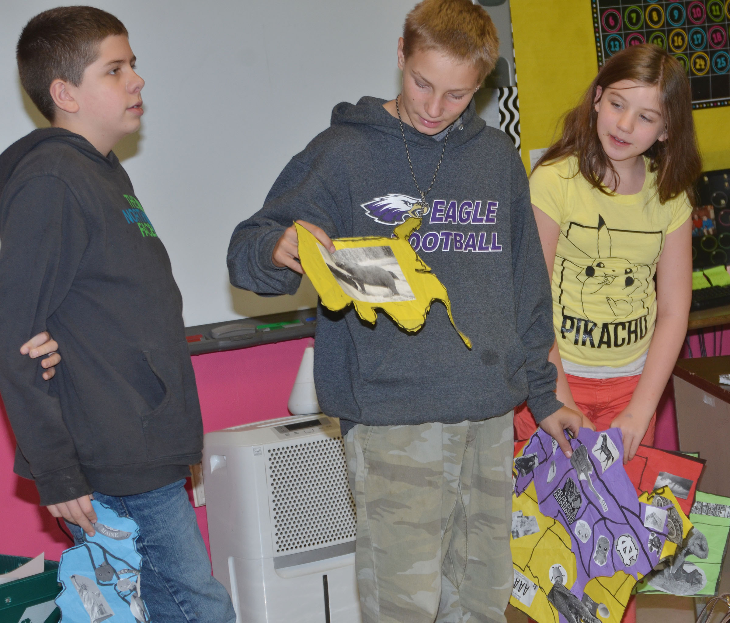 From left, CMS sixth-graders Chris Clark, Damon Johnson and Mikaela Scharbrough discuss their group's map.