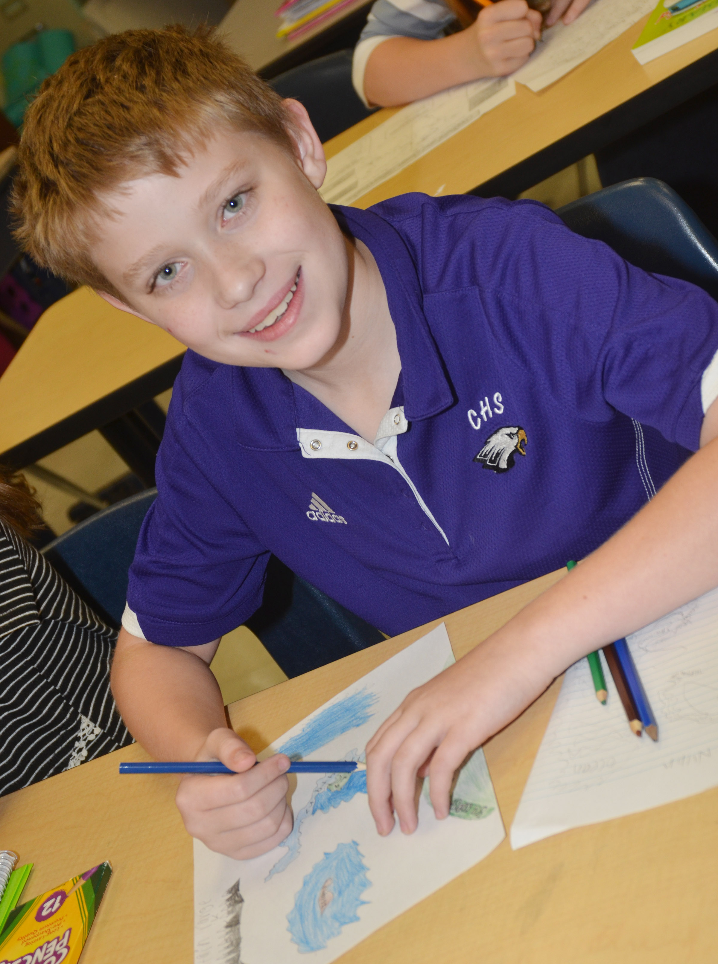CMS sixth-grader Willie Nunn smiles as he colors his children's book.