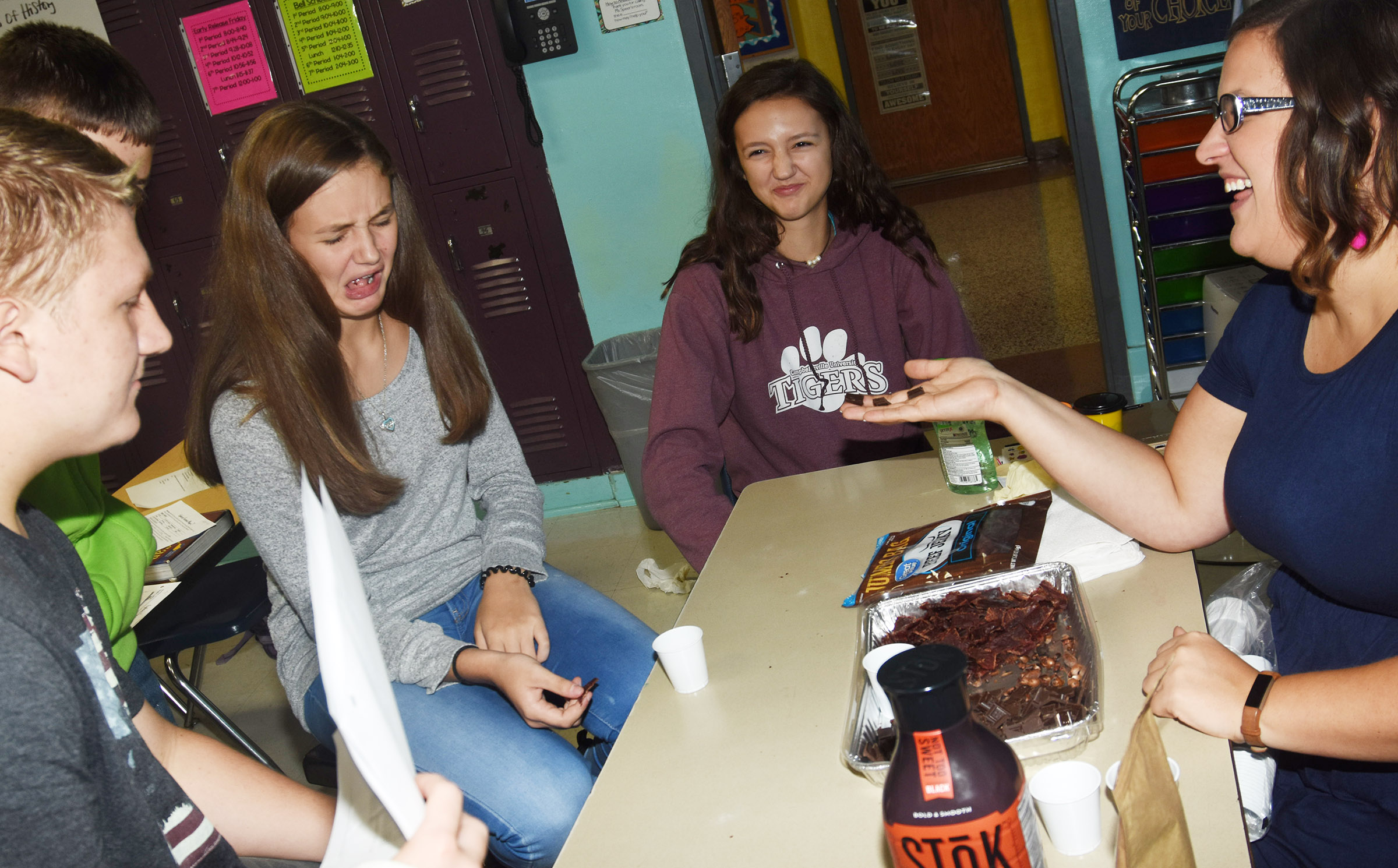 CMS teacher Robbilyn Speer laughs as her students, from left, eighth-graders Levi Dicken, Haylee Allen and Bri Hayes, react as they sample dark chocolate, which the Native Americans introduced to the Europeans.