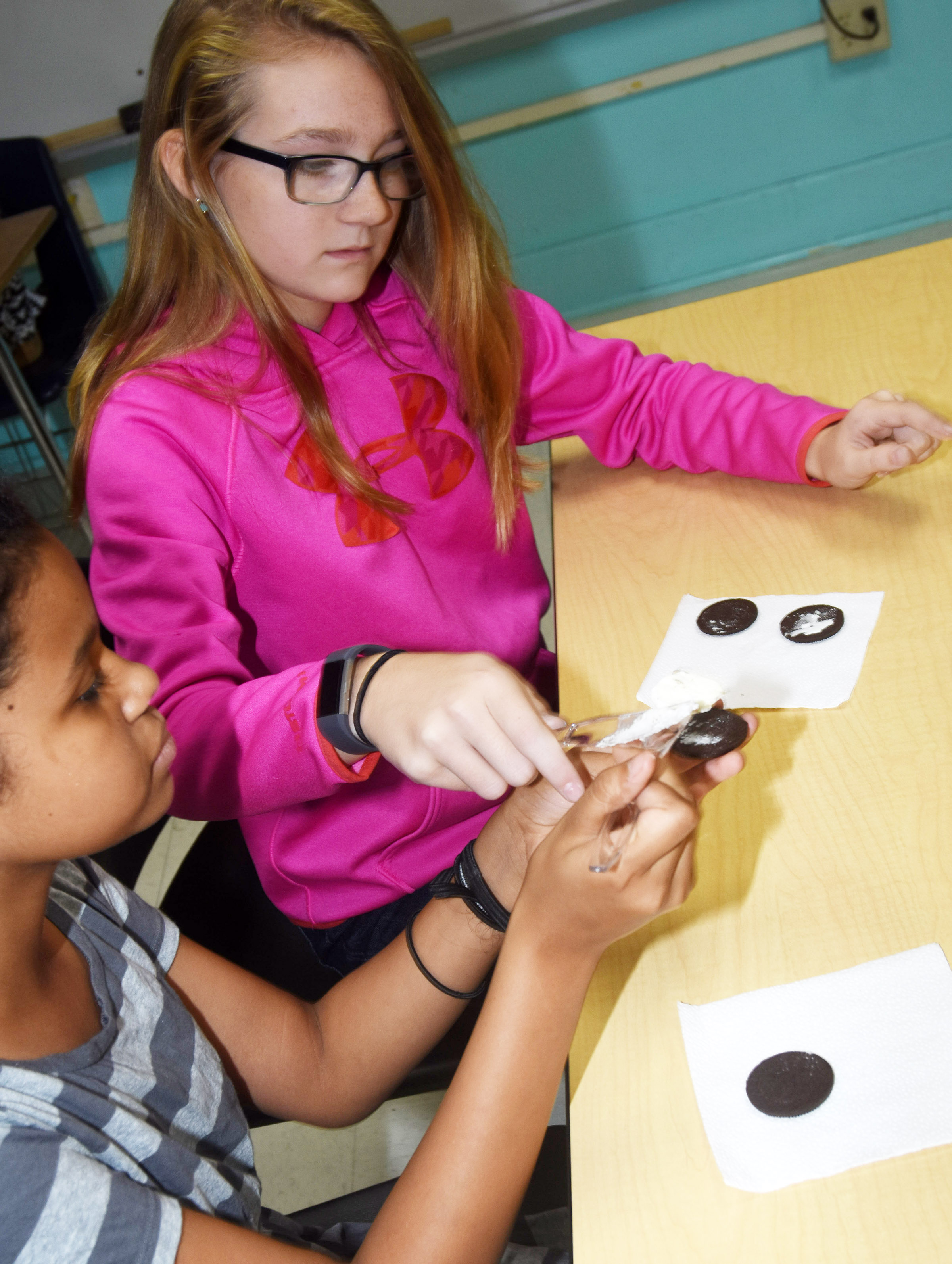 CMS sixth-graders Destiny Bradley, at left, and Lilyan Murphy use cookies to make the phases of the moon.
