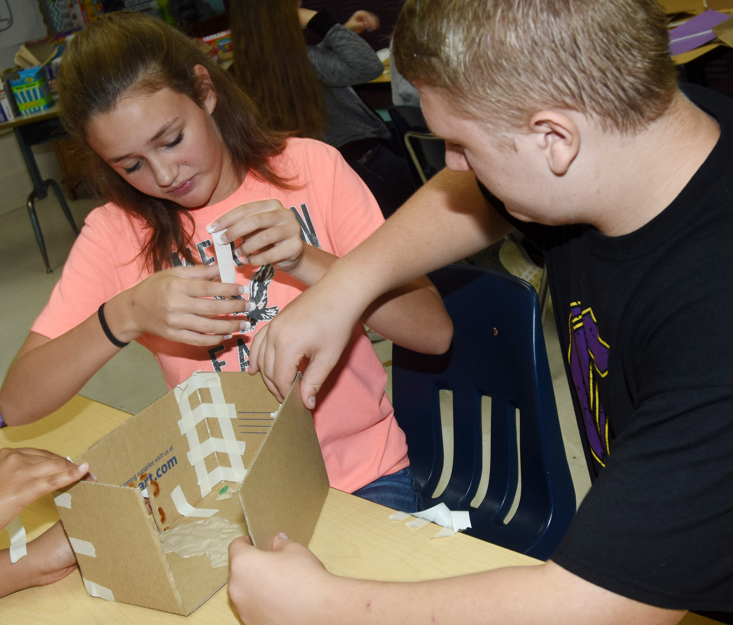 CMS eighth-graders Haylee Allen, at left, and Levi Dicken make a plank house.