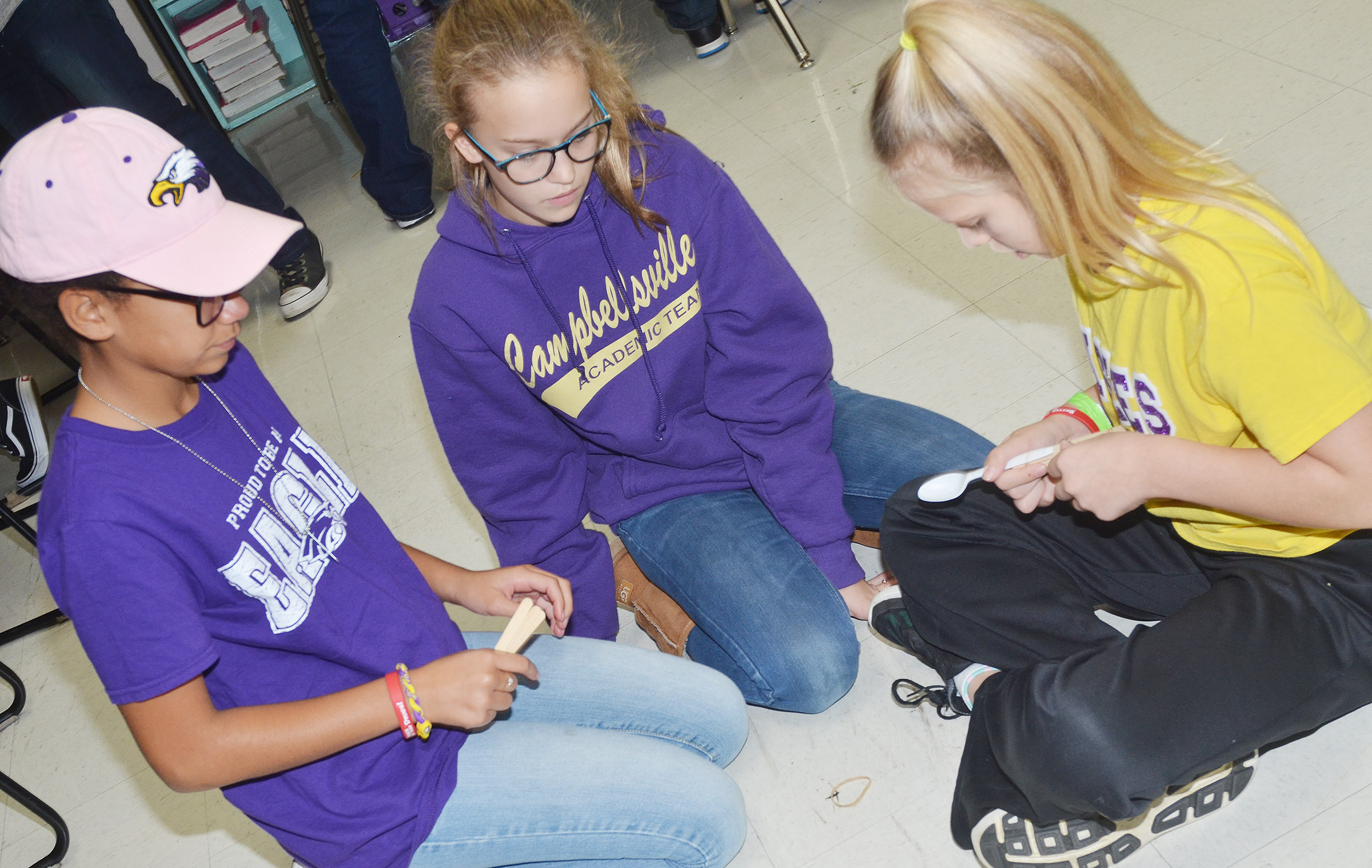 CMS sixth-graders, from left, Keely Thompson, Chloe Thompson and Gabby Bright build their catapult.