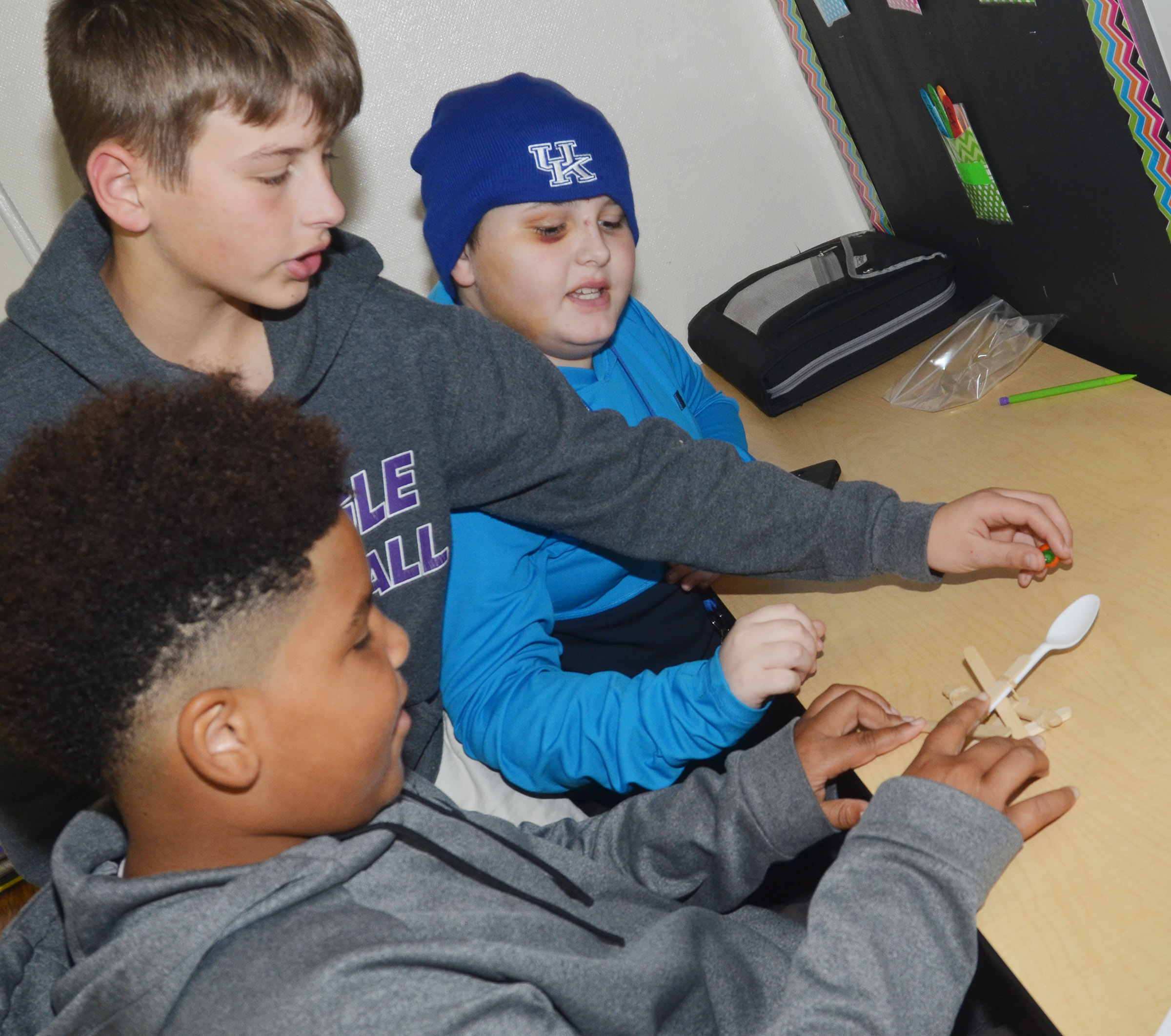 From left, CMS sixth-graders Devin Kinser, Jaxon Sidebottom and Dawson Creason prepare to launch their catapult.