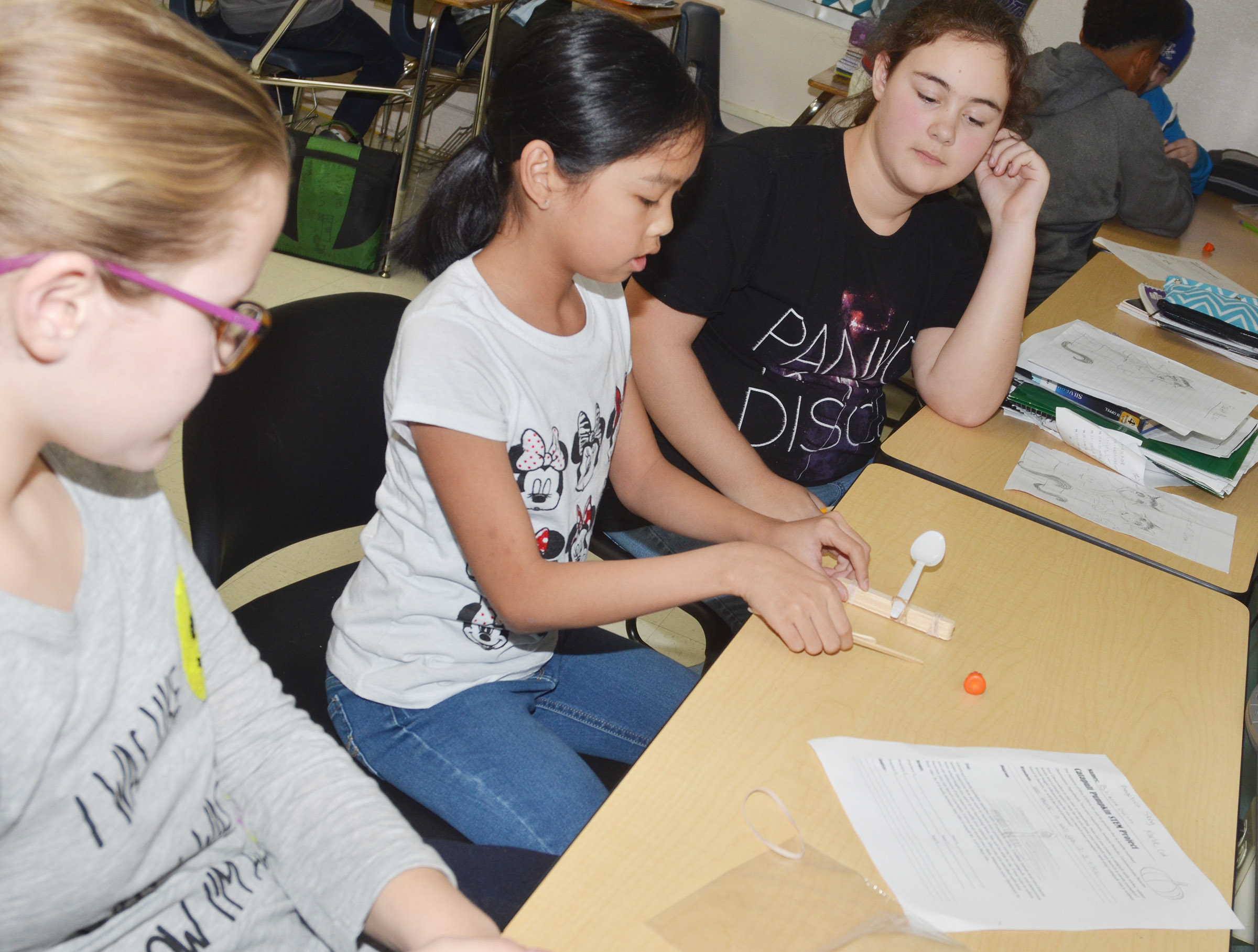 CMS sixth-graders, from left, Karlie Cox, Angelica Seng and Brianna Dobson prepare to launch their catapult.
