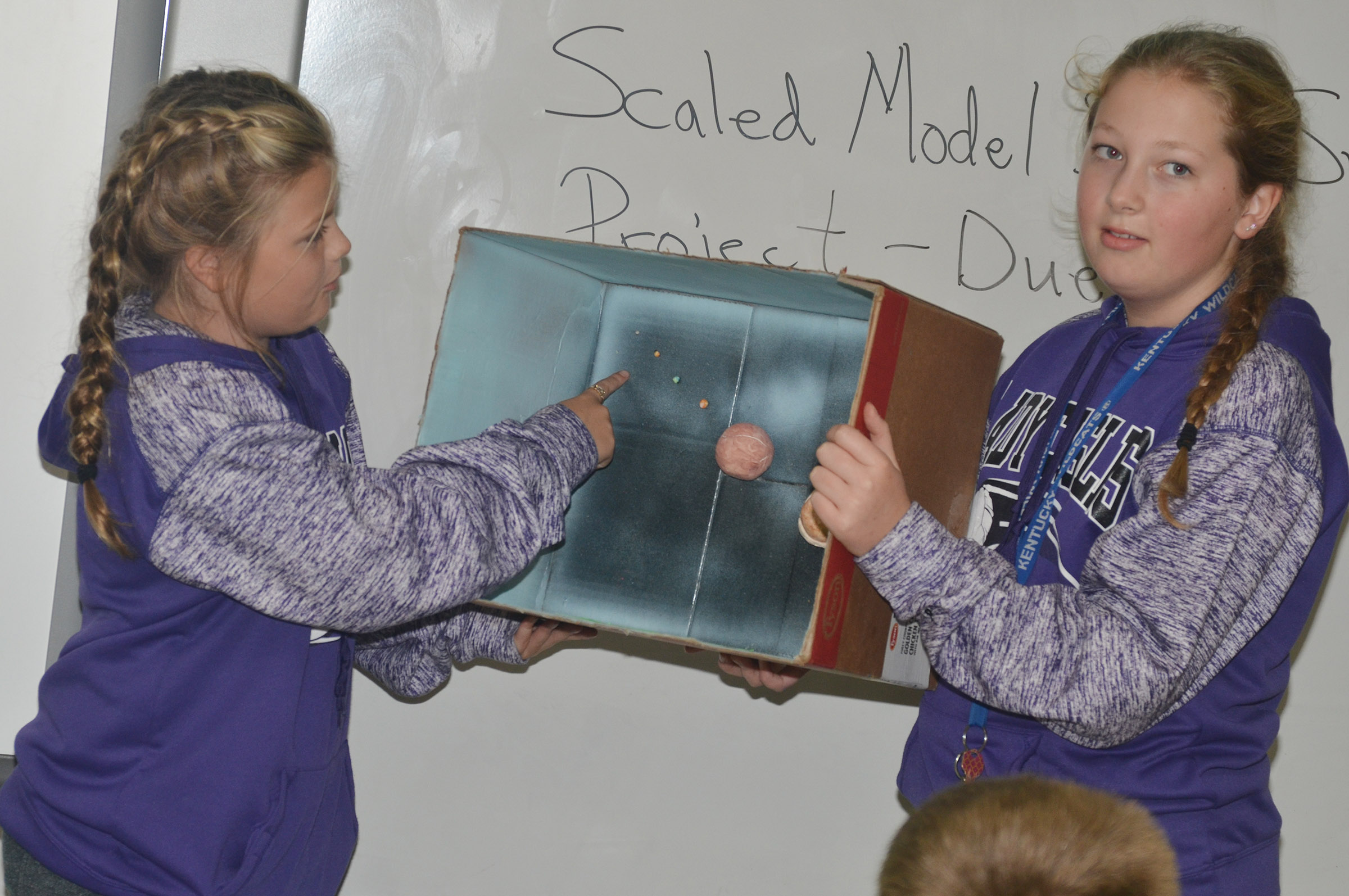 CMS sixth-graders Ellington Gowin, at left, and Ava Hughes present their solar system model.