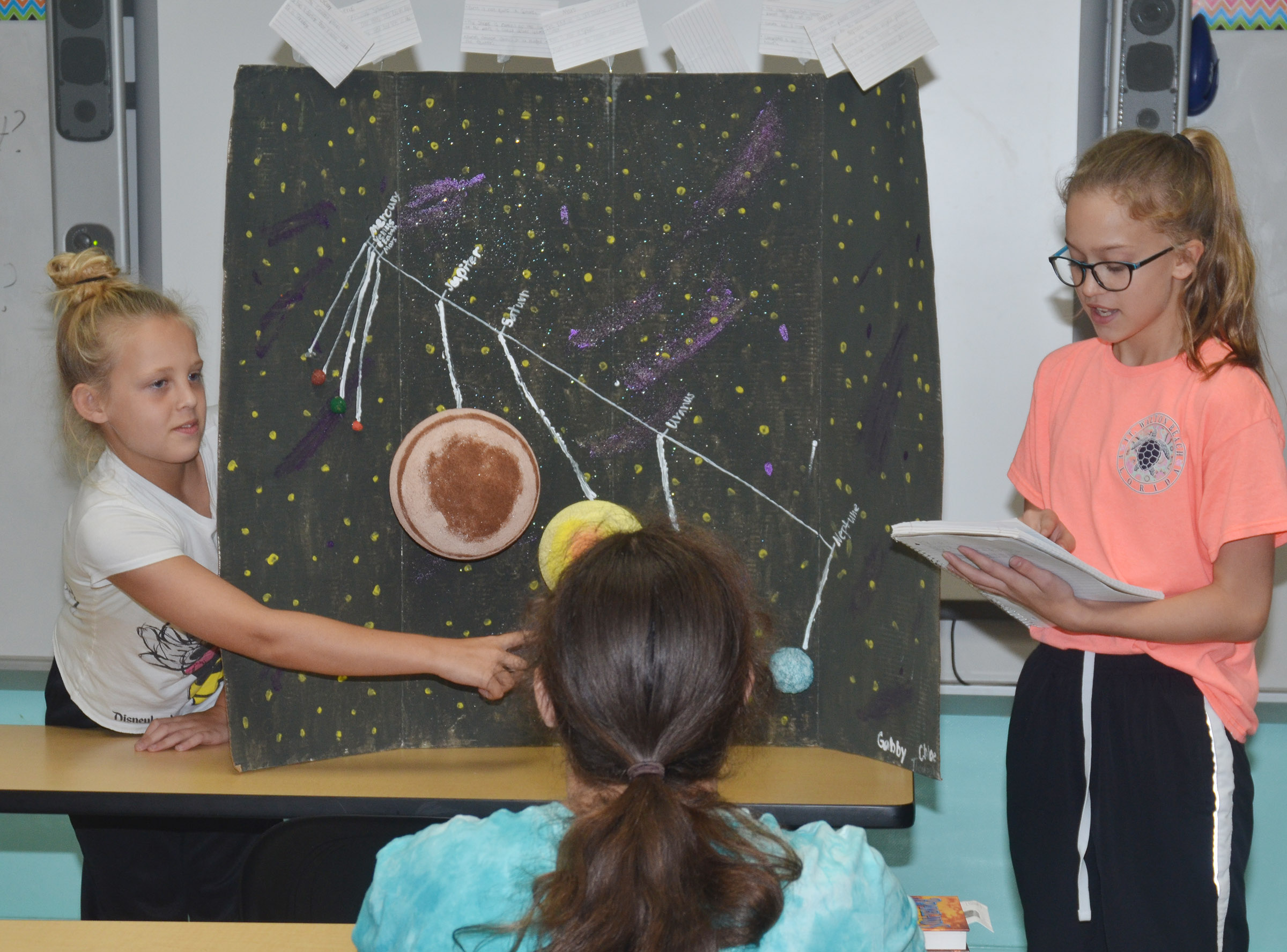 CMS sixth-graders Gabby Bright, at left, and Chloe Thompson present their solar system model.
