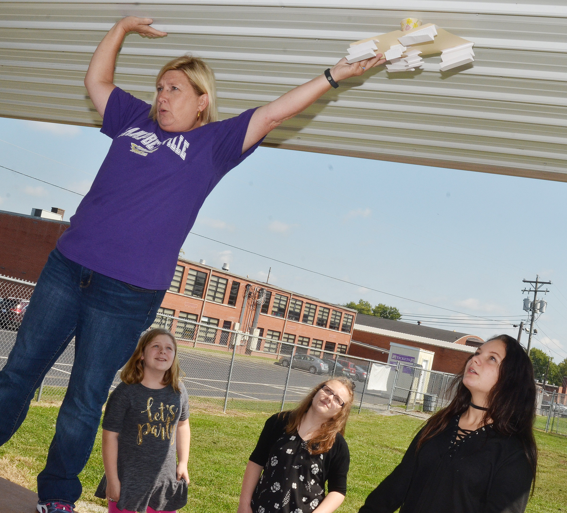 CMS sixth-grade teacher Jan Speer drops a spacecraft, as, from left, Alexis Sharp, Ellington Gowin and Margaret Johnson watch.