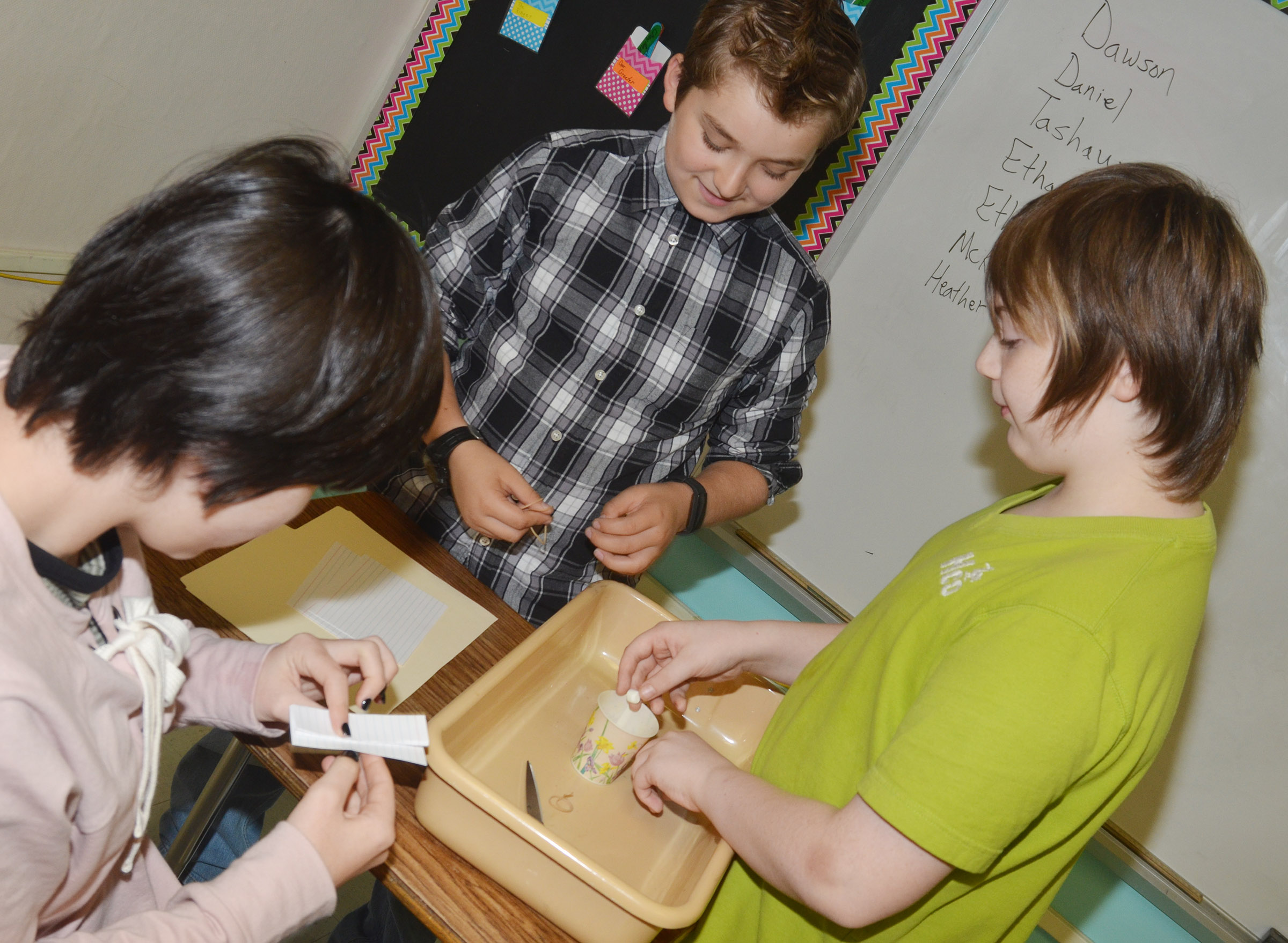 CMS sixth-graders, from left, K.J. Forbis, Nathan McFarland and Sully Streeval build their spacecraft.