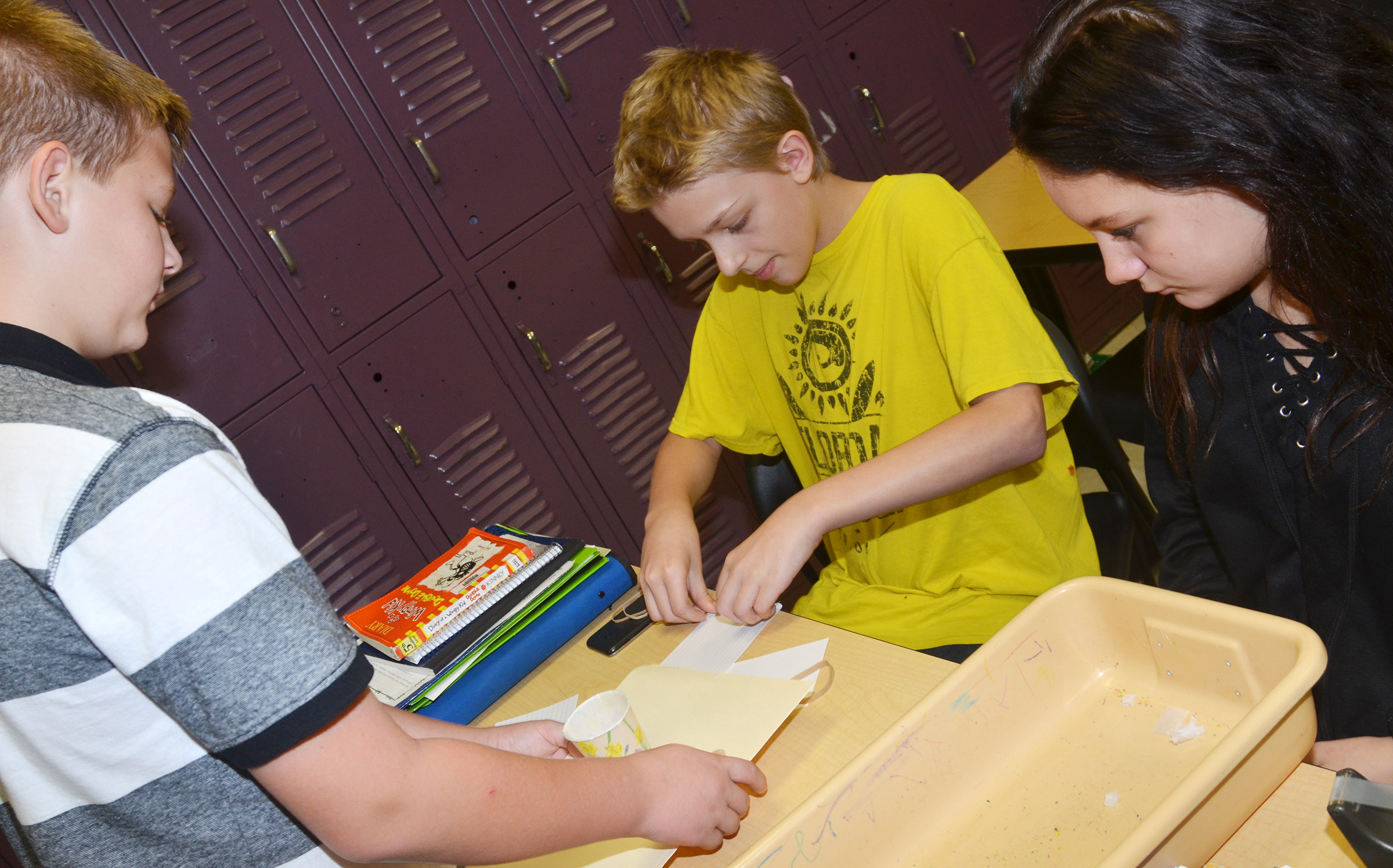 From left, CMS sixth-graders Jesse King, Jacob Releford and Margaret Johnson build their spacecraft.