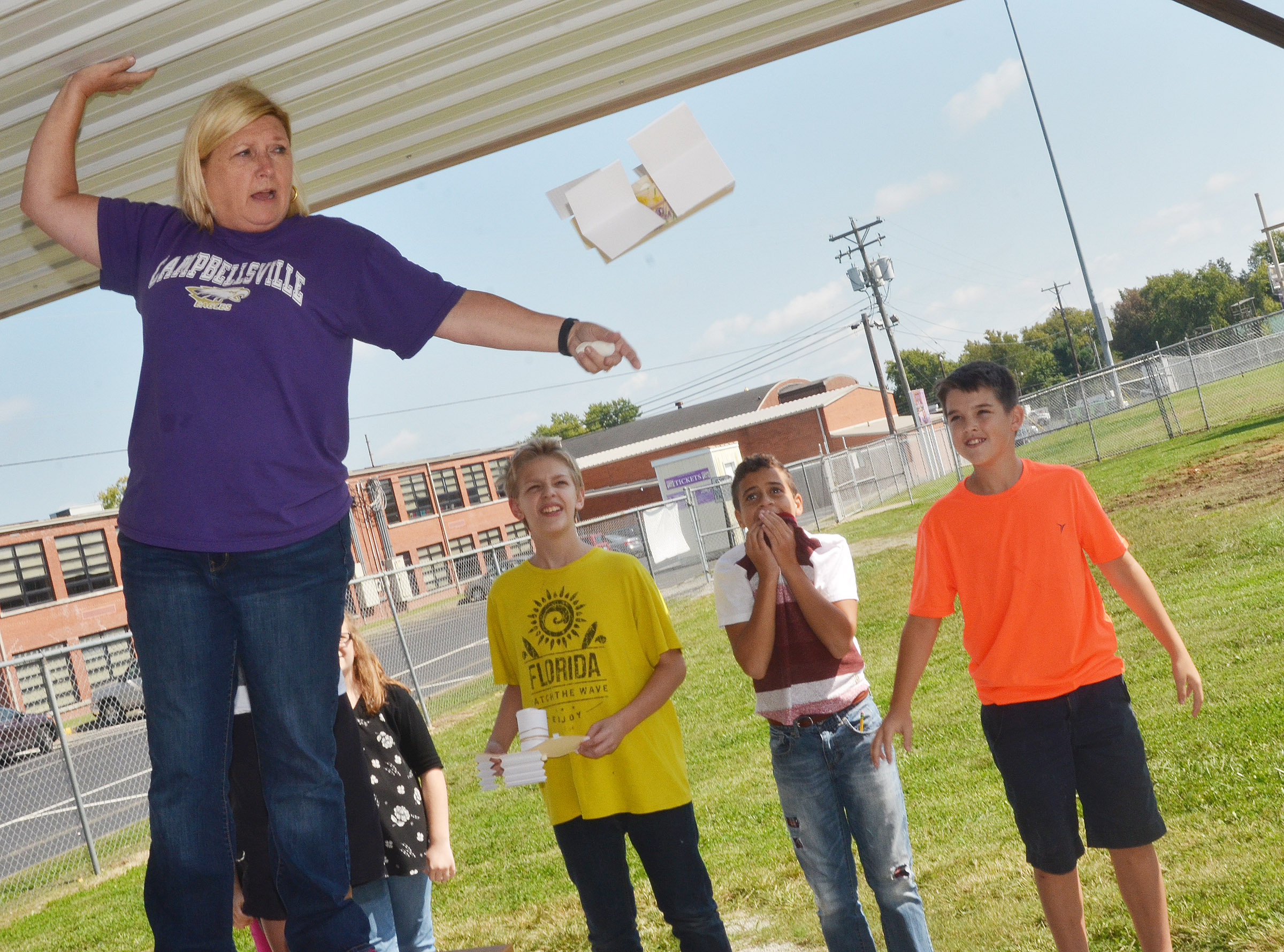 CMS sixth-grade teacher Jan Speer drops a spacecraft, as, from left, Jacob Releford, Tucker Cartwright and Kaden Bloyd watch.