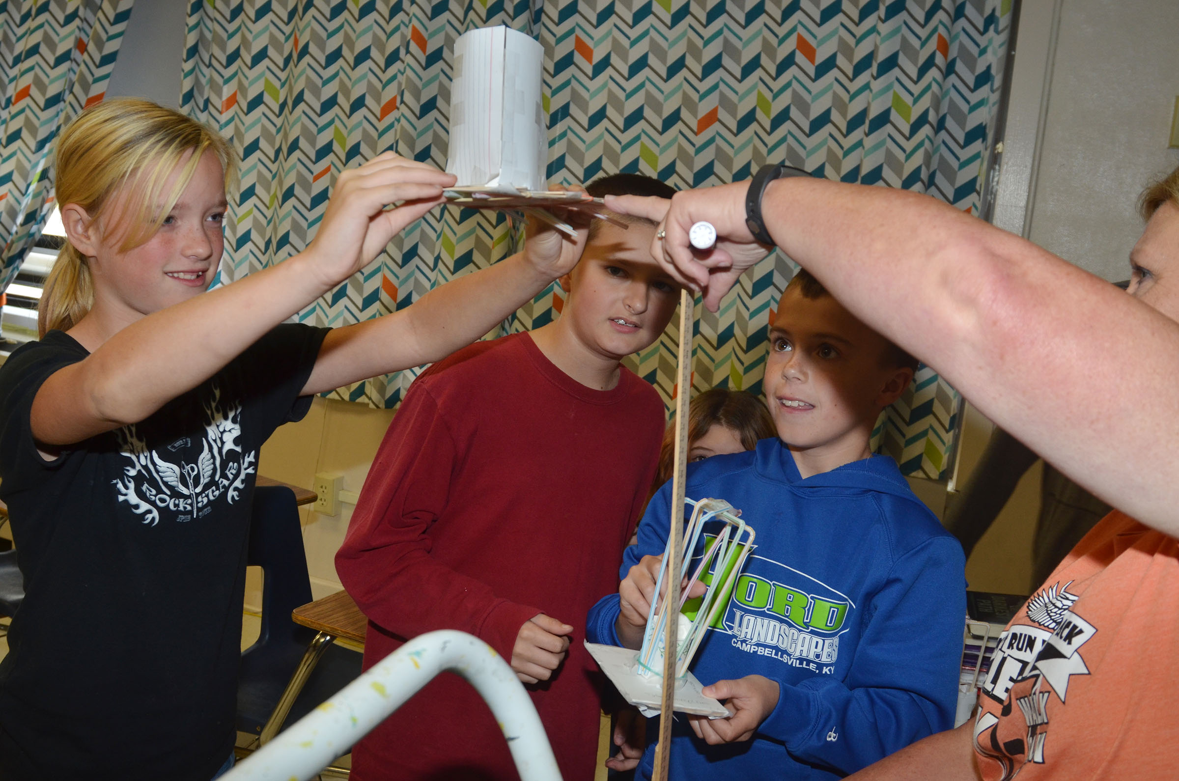 With some help from teacher Jan Speer, CMS sixth-grader Tonya Parker drops her group's spacecraft, as classmates Tyler Booth and Chase Hord watch.