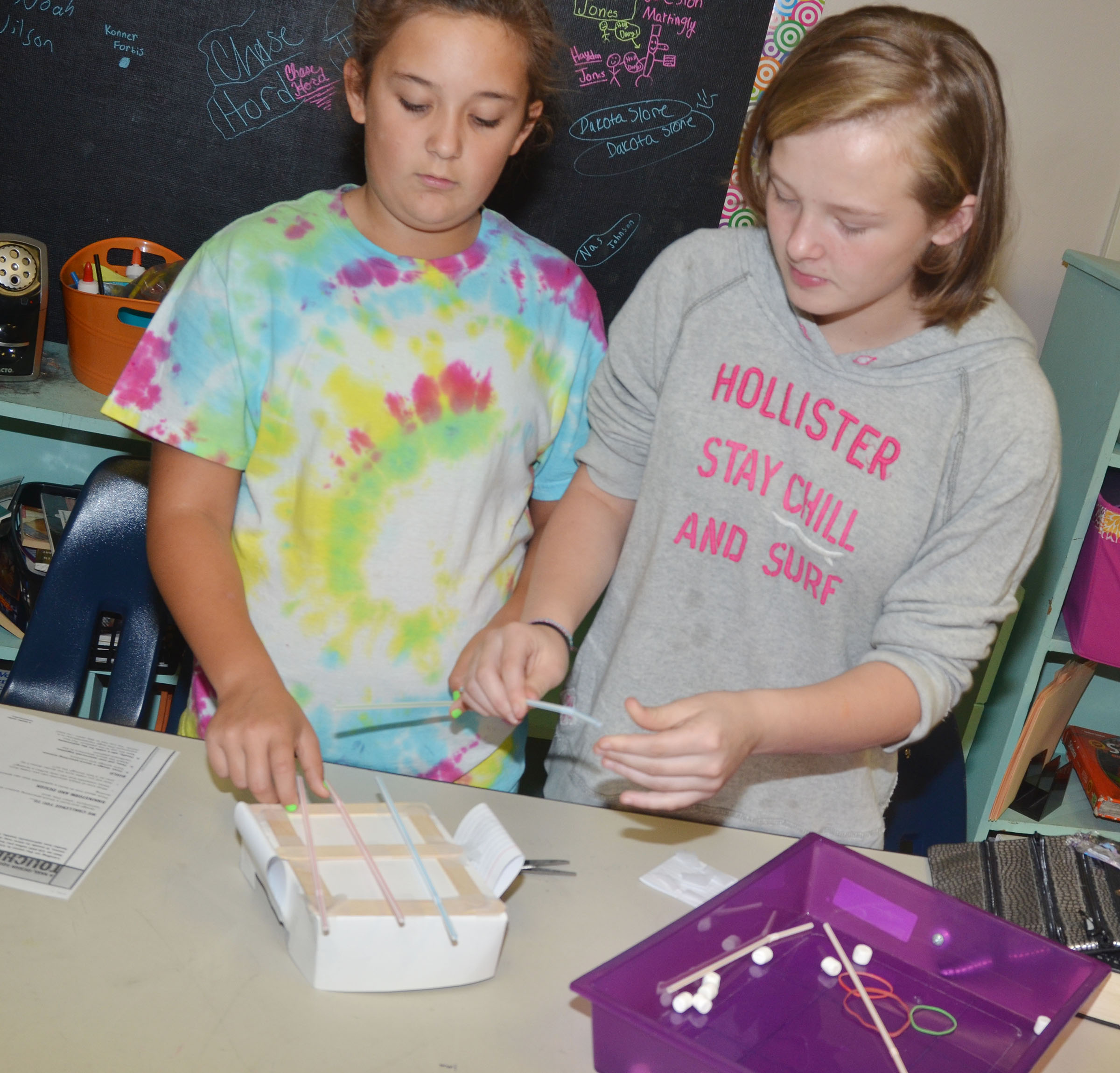 CMS sixth-graders Briana Davis, at left, and Davanna Reardon work on their spacecraft.