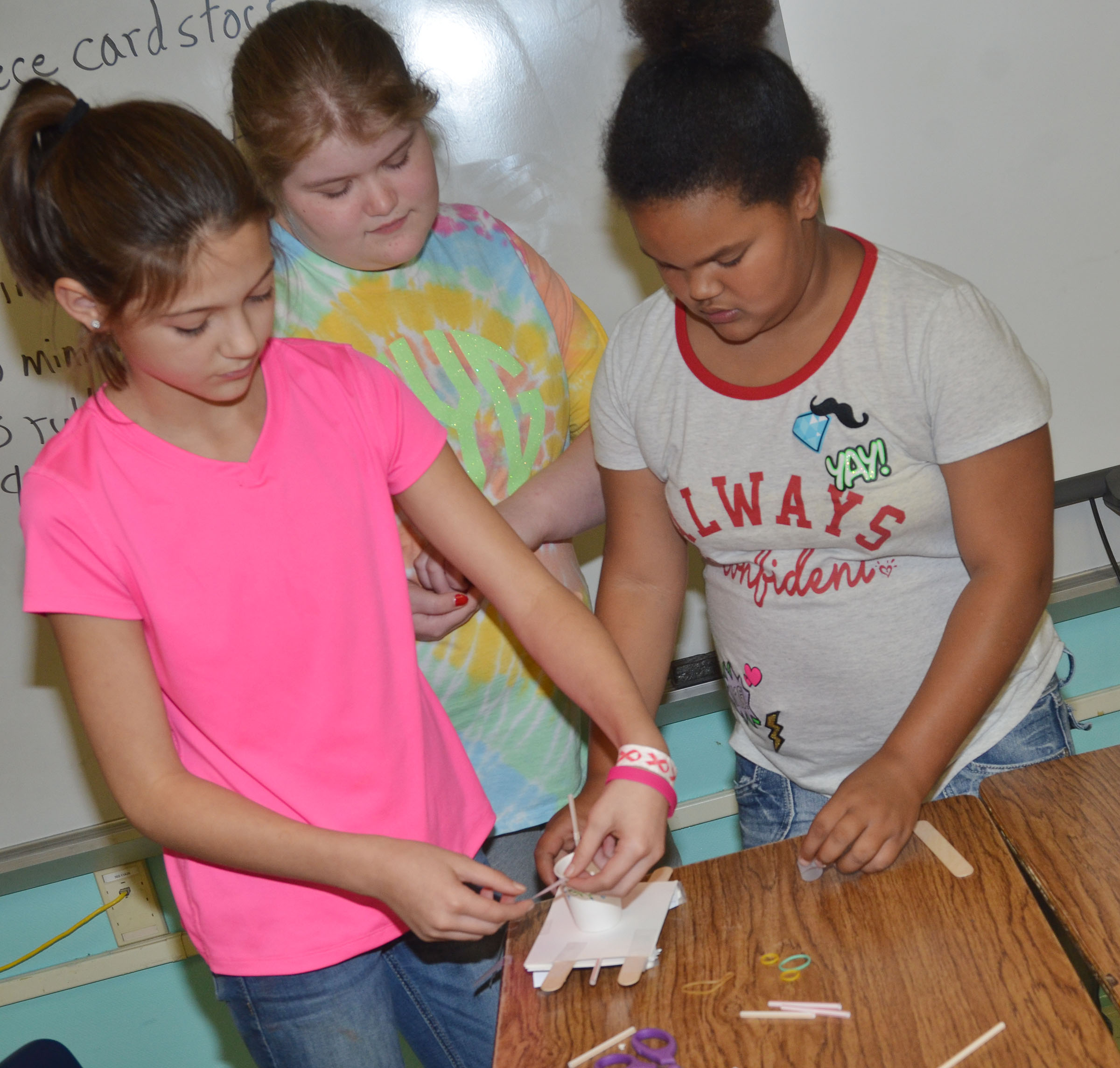 From left, CMS sixth-graders Emily Shuck, Aubrey Young and Alissa Lofton build their spacecraft.