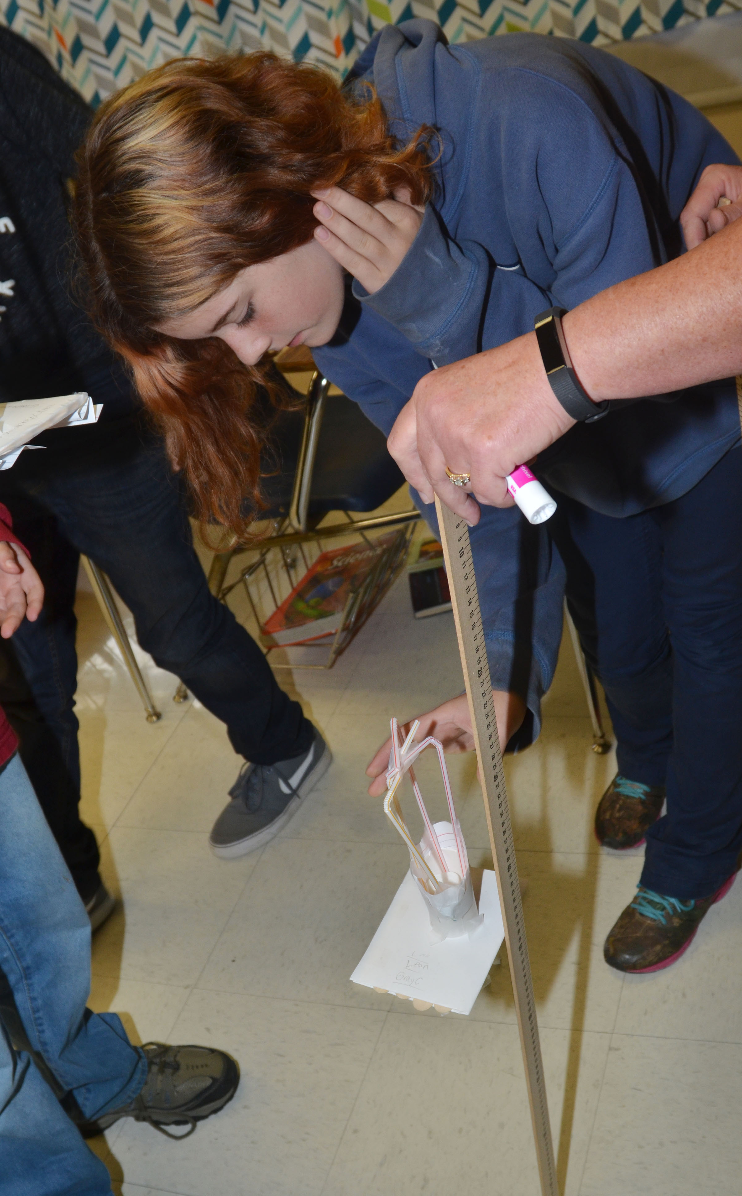 CMS sixth-grader Kaylee Coffman tests her group's spacecraft, with help from teacher Jan Speer.