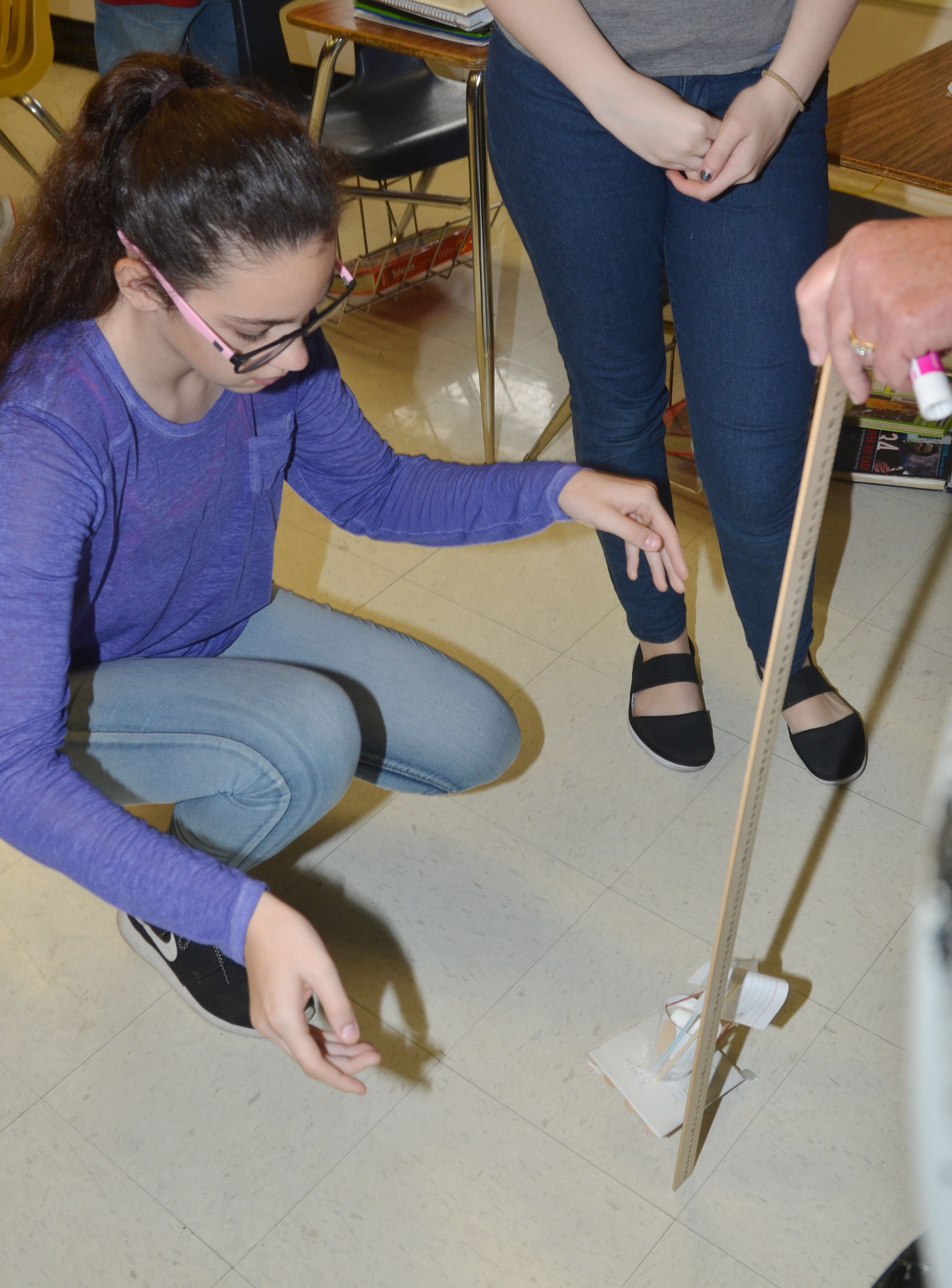 CMS sixth-grader Mary Russell tests her group's spacecraft, with help from teacher Jan Speer.