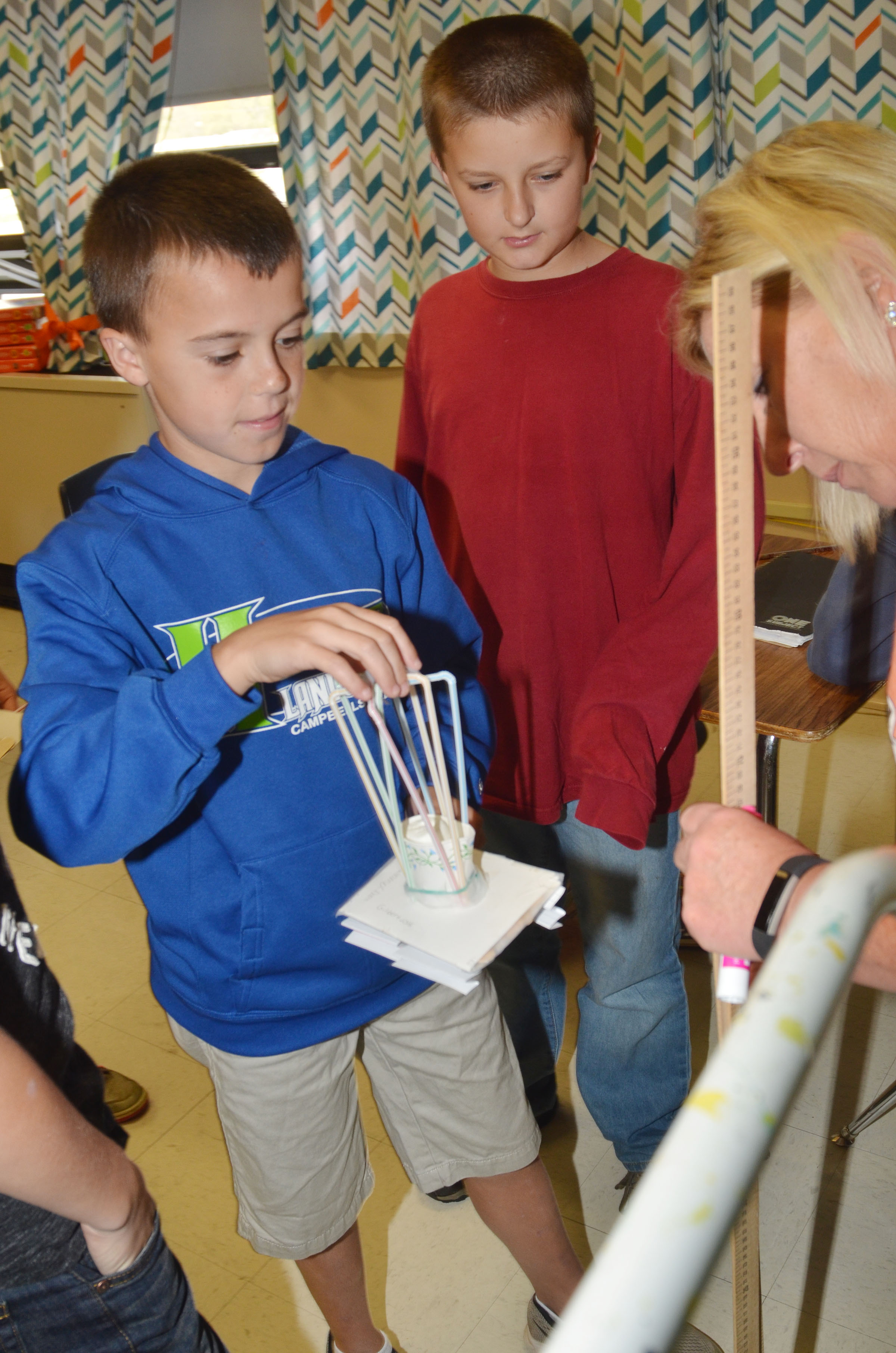 CMS sixth-graders Chase Hord, at left, and Logan Marples test their group's spacecraft, with help from teacher Jan Speer.