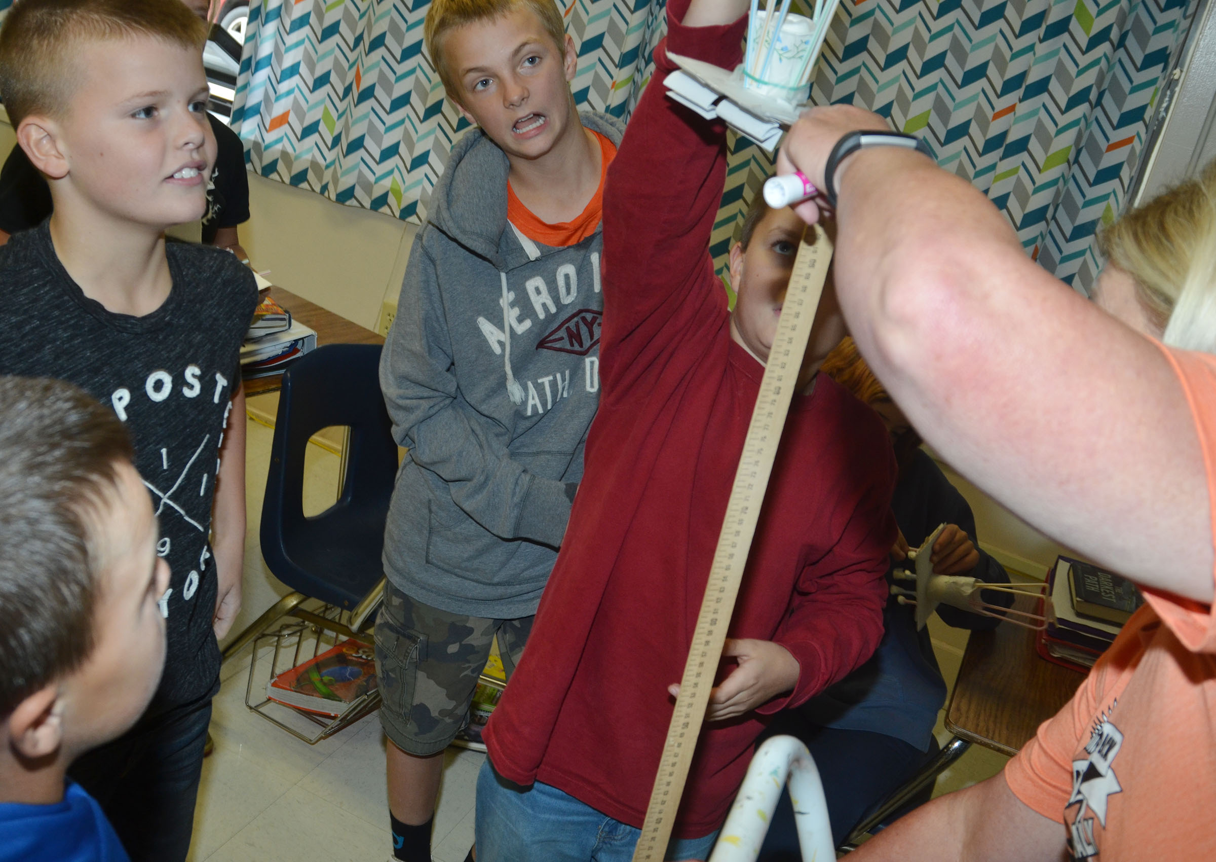 With some help from teacher Jan Speer, CMS sixth-grader Tyler Booth drops his group's spacecraft as his teammates, from left, Chase Hord, Konner Forbis and Logan Marples watch.