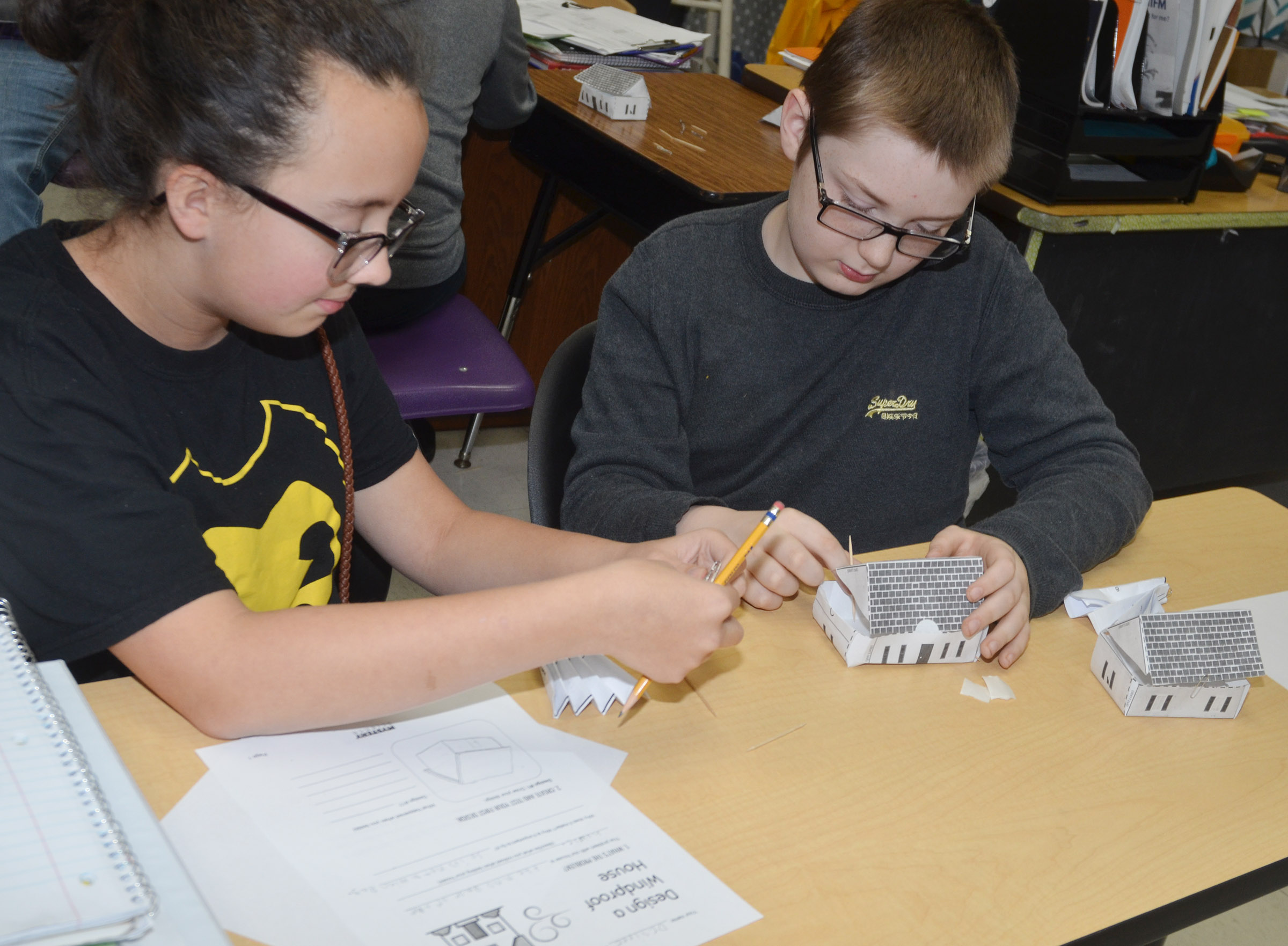 CMS sixth-graders Desiree Kouns, at left, and Sully Streeval test their houses to see if they are windproof.